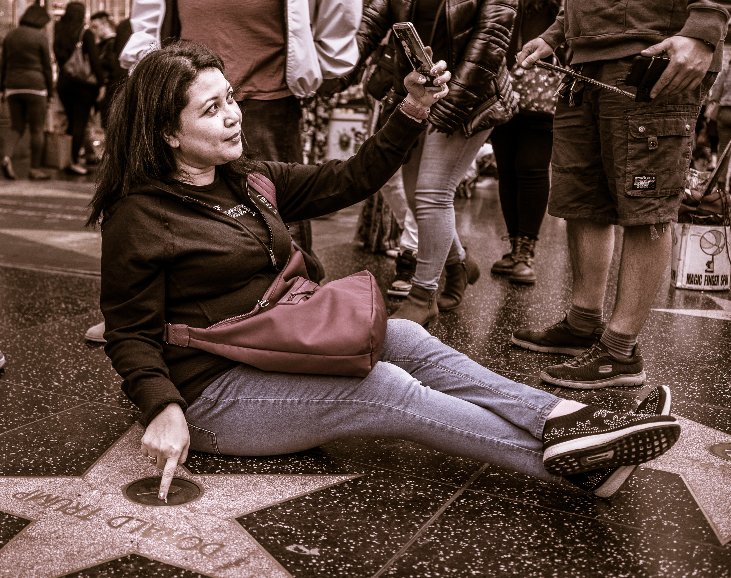 a woman sits on the ground next to Donald Trump's star on Hollywood Blvd. She holds her cell phone high in the air to capture the scene. With her other hand she points to Donald Trump's name and smiles.