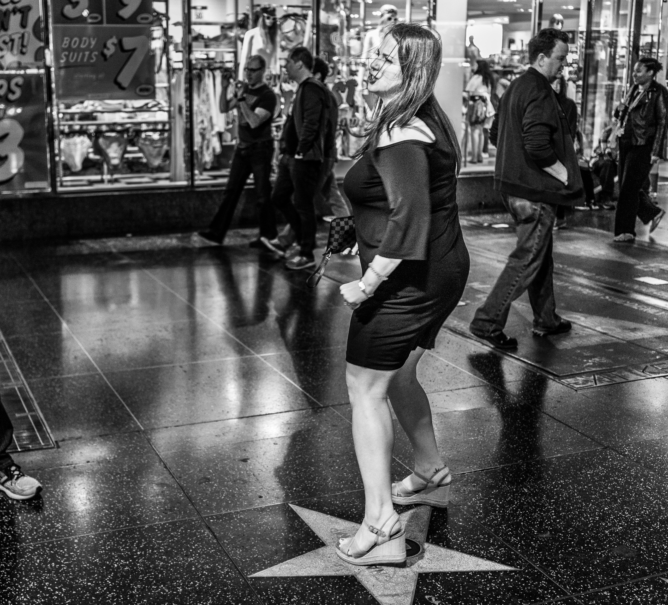 a woman stomps and twists her feet on Donald Trump's star on Hollywood Blvd.