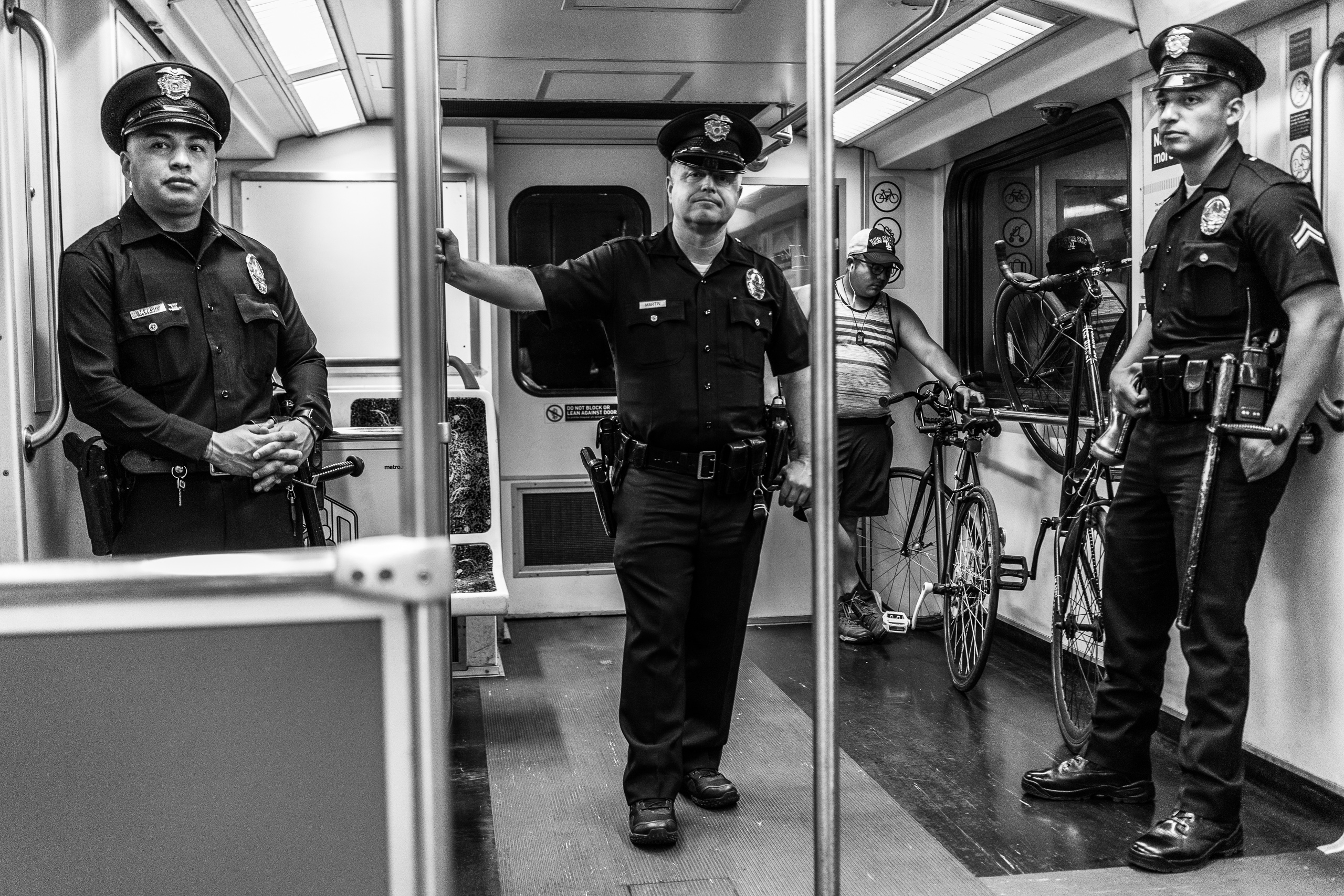 3 LAPD officers stand in a Metro Red Line train car