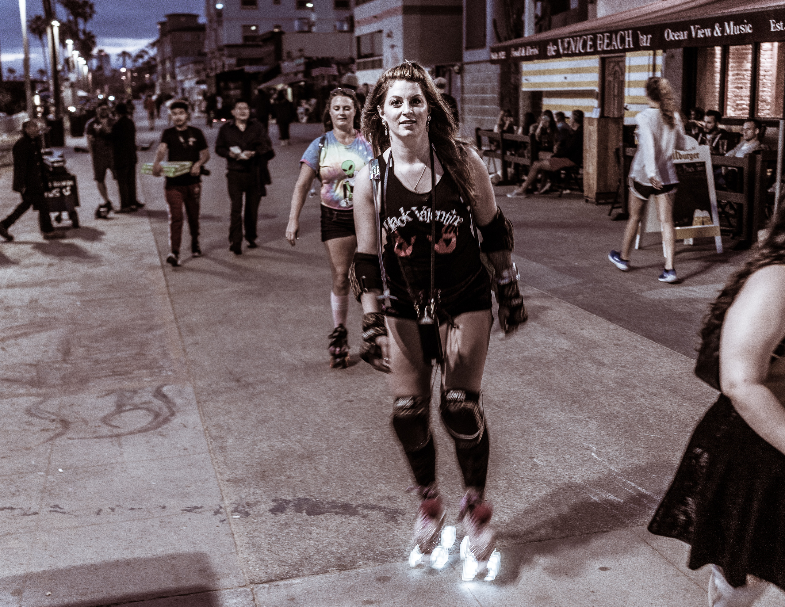 "a woman in a ""Black Valentine"" t-shirt skates down the Venice Beach, CA Boardwalk at dusk. The wheels of her skates light up as she passes ""The Venice Beach Bar"""