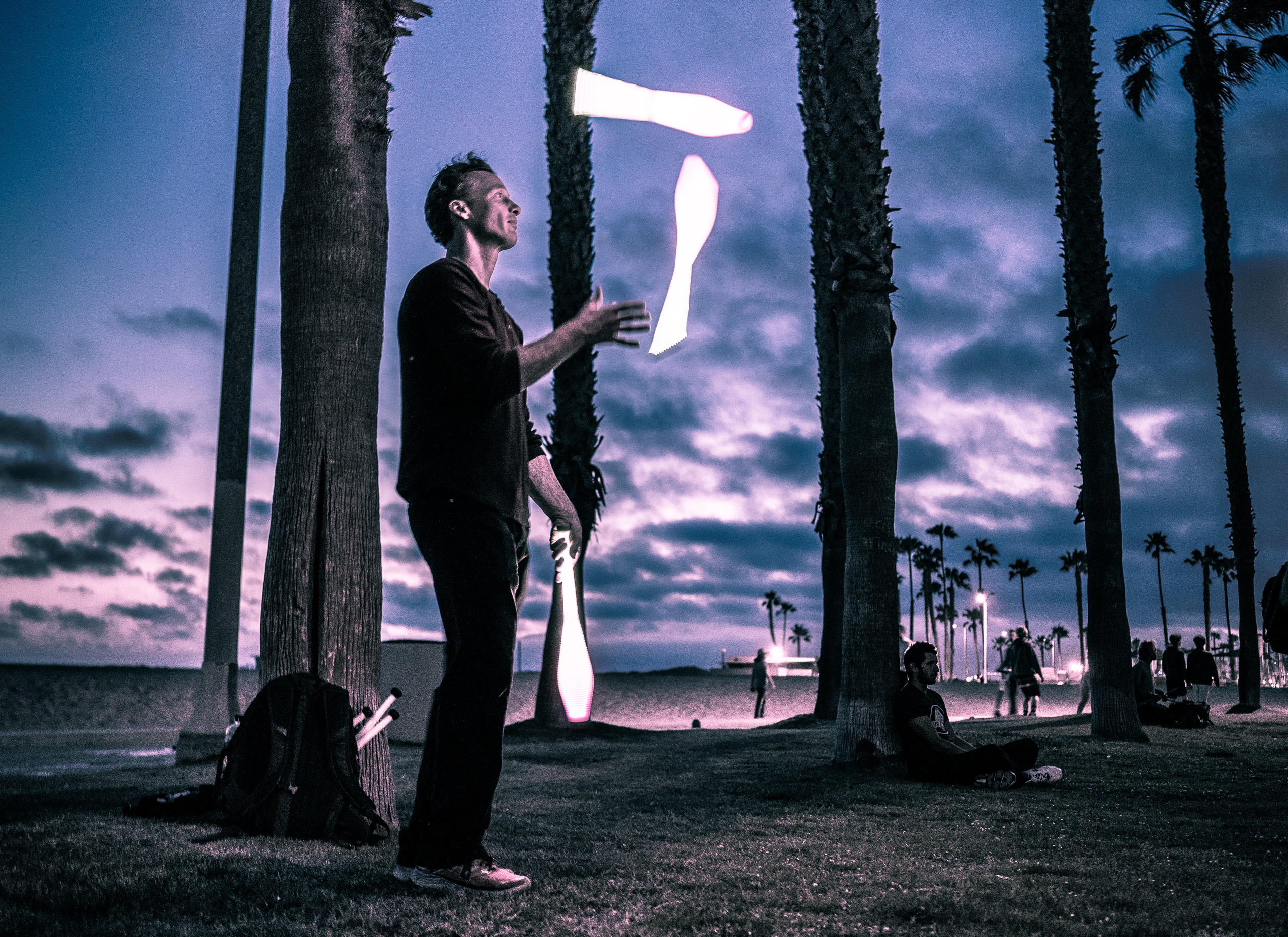 "A guy in the park at Venice Beach juggling illuminated clubs at the ""blue hour"""
