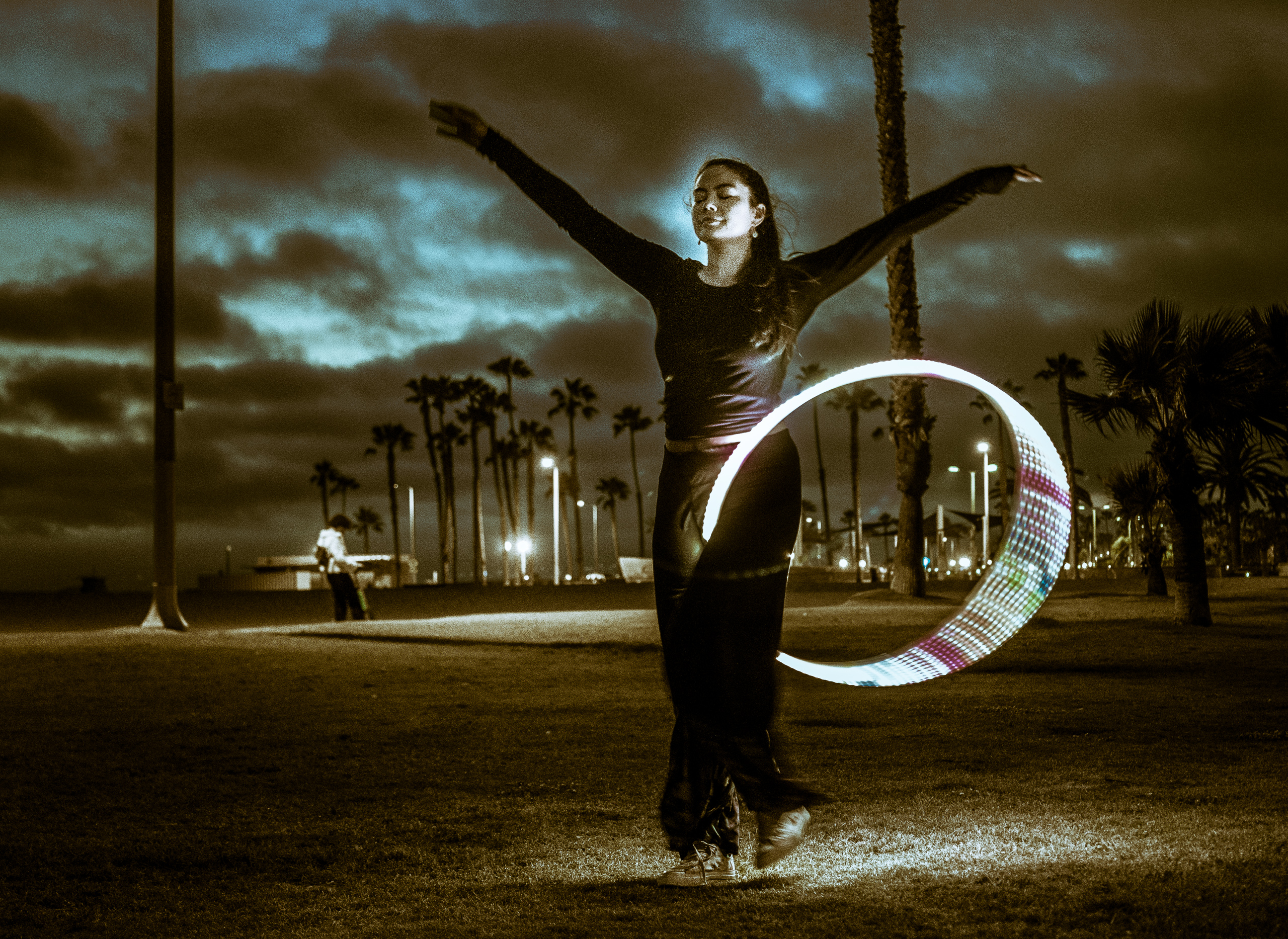 "Photos of the Venice Glow Flow group in Venice Beach, California. A cloudy sky over the Pacific Ocean in the ""blue hour"" after sunset. A woman works with an LED hoop."