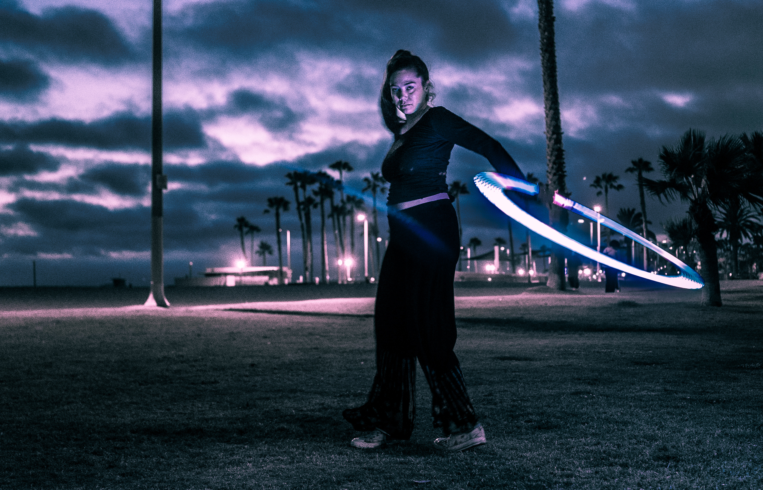 "A juggler with an LED hoop working out in Venice Beach at the ""blue hour"" after sunset. Her face is illuminated by her LED hoop and there is a cloud-filled sky behind her. The group is called Venice Glow Flow."