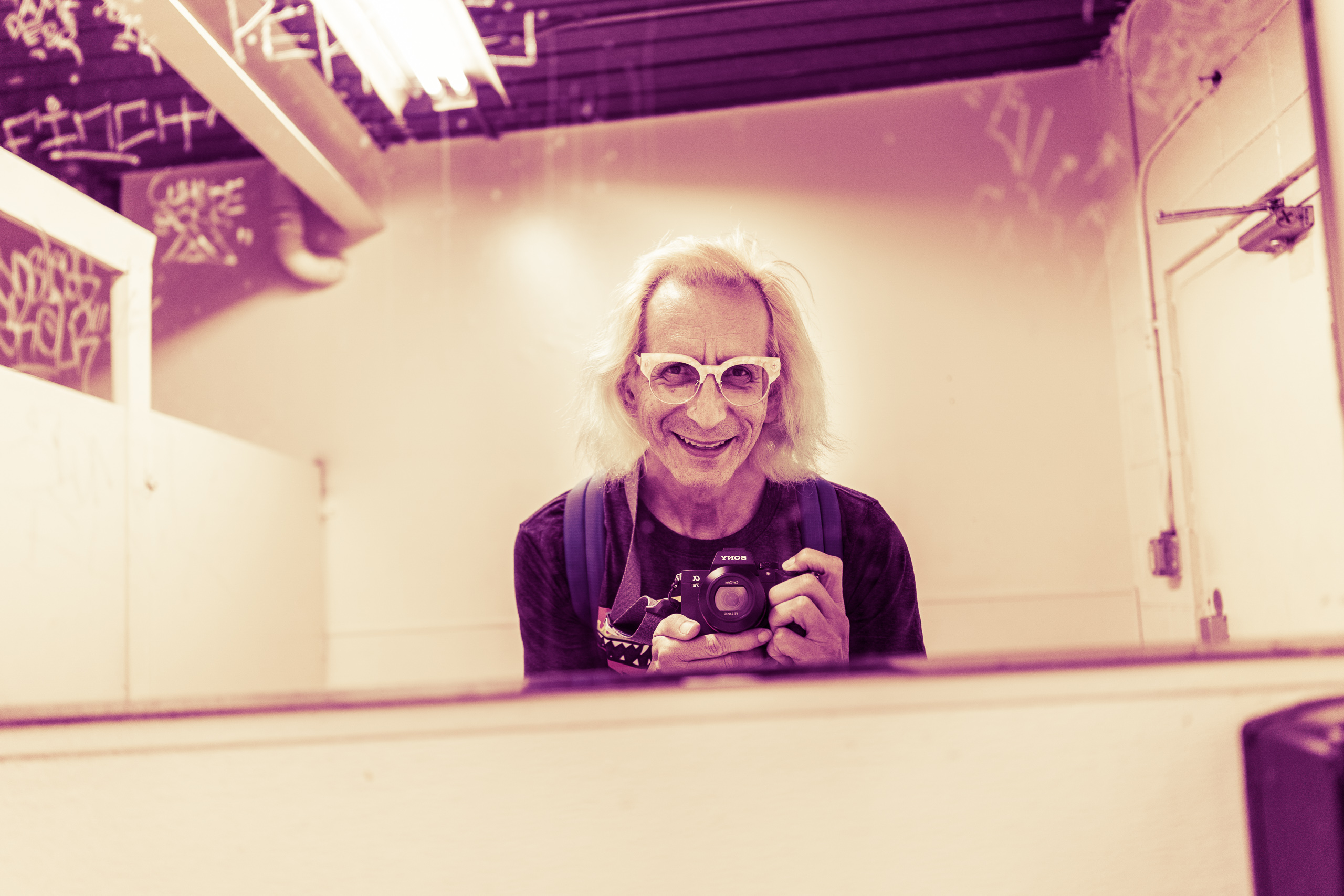 Glenn Zucman taking a selfie in the mirror of the men's room in the parking lot at 26th Street / Bergamot Art Center in Santa Monica and at the  26th St / Bergamot Station station of the LA Metro Expo Line. Zucman's figure is cut off at the bottom by the bottom of the mirror. Around the periphery the mirror glass is etched with various tags.