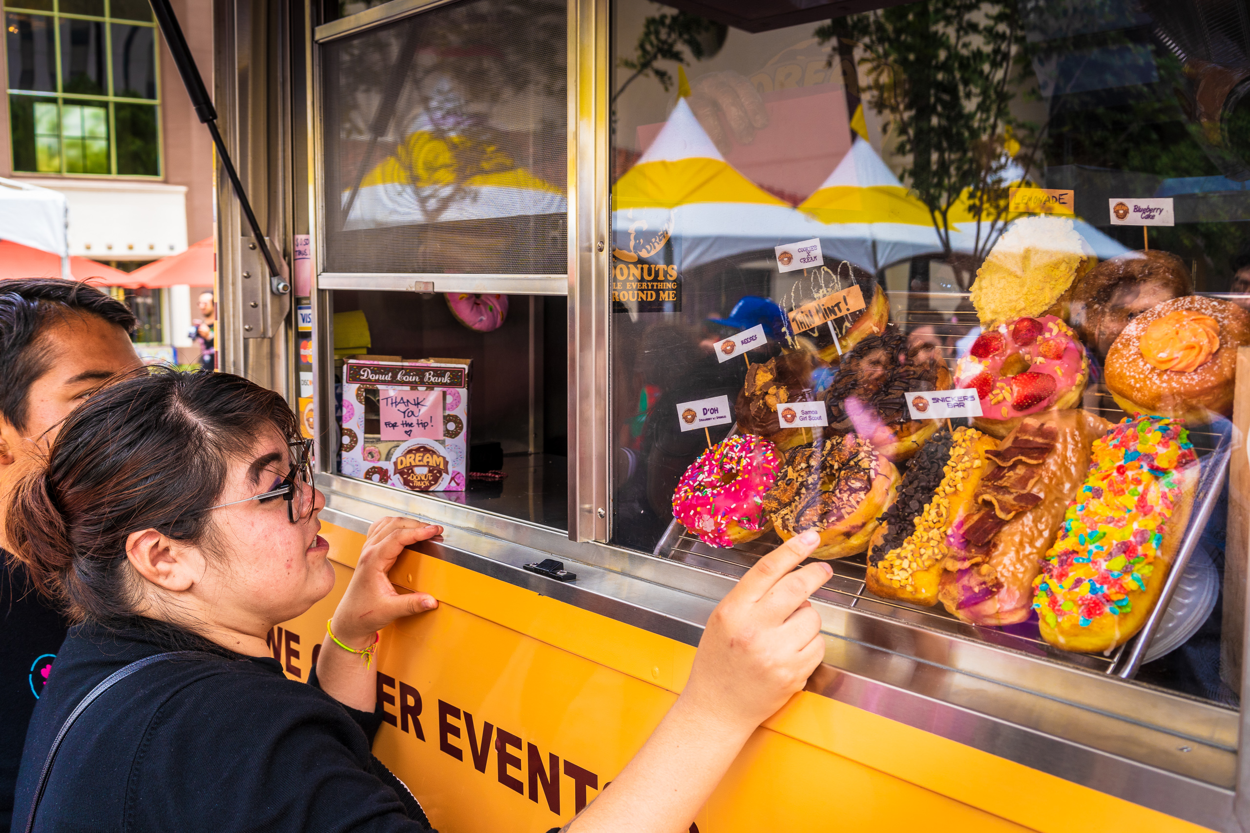 a woman orders a Samoa Girl Scout donut from the Dream Donut Truck at Union Station in Los Angeles on Donut Day