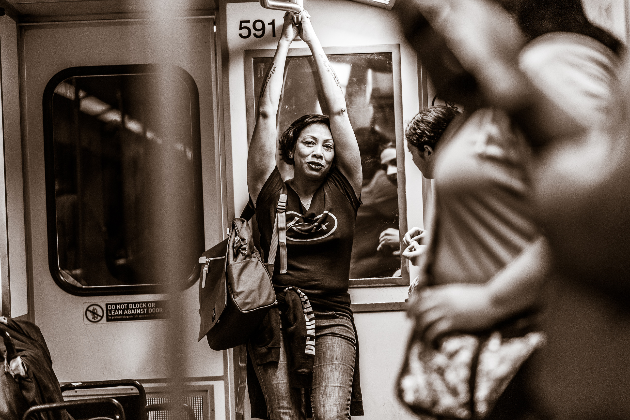 a woman stands at the end of a Metro Red Line heavy rail car underground in Hollywood. She had both arms over her head holding onto a hand rail on the train car ceiling