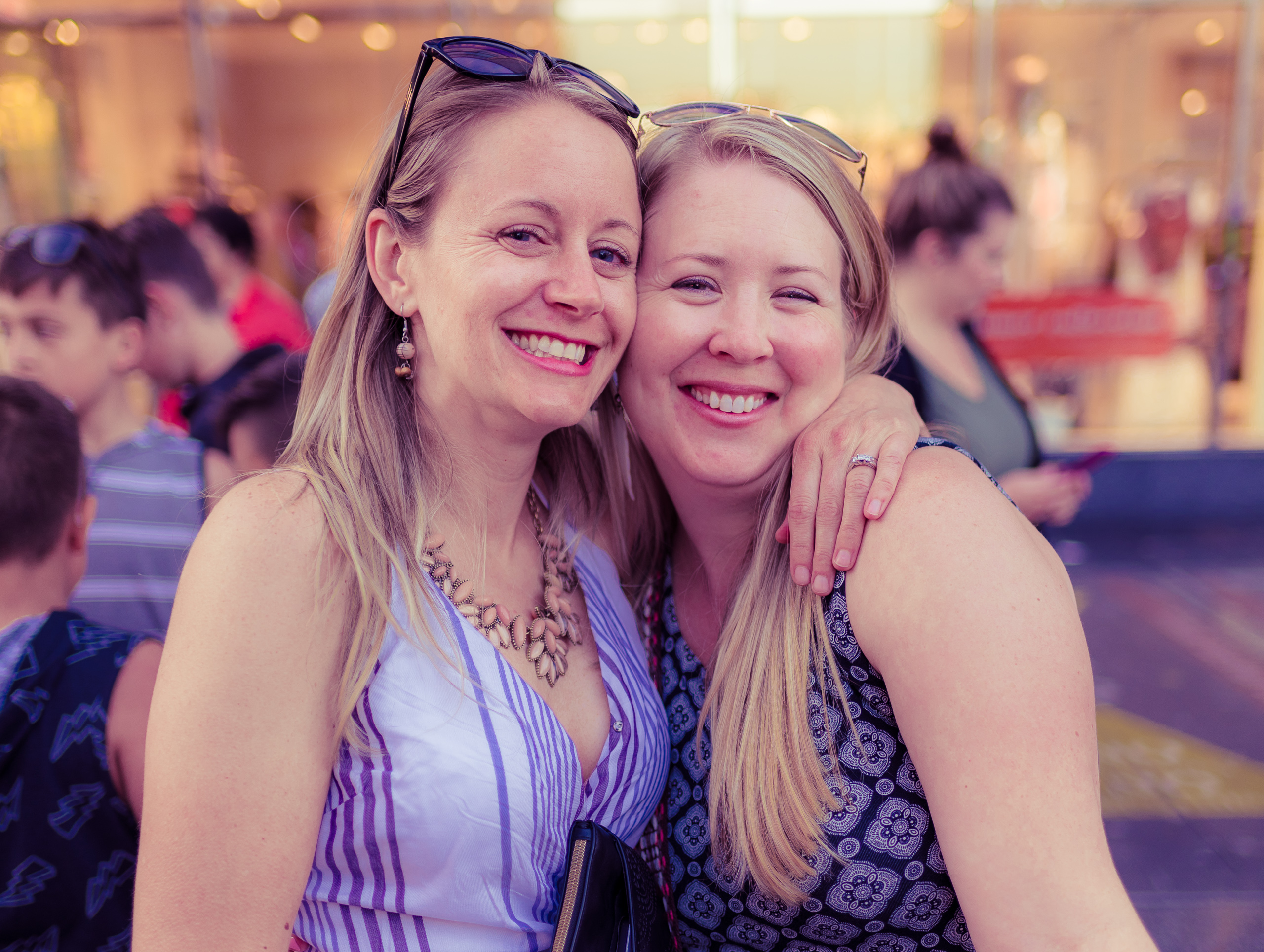 two blonde, fair complected, women embrace and smile in the afternoon glow