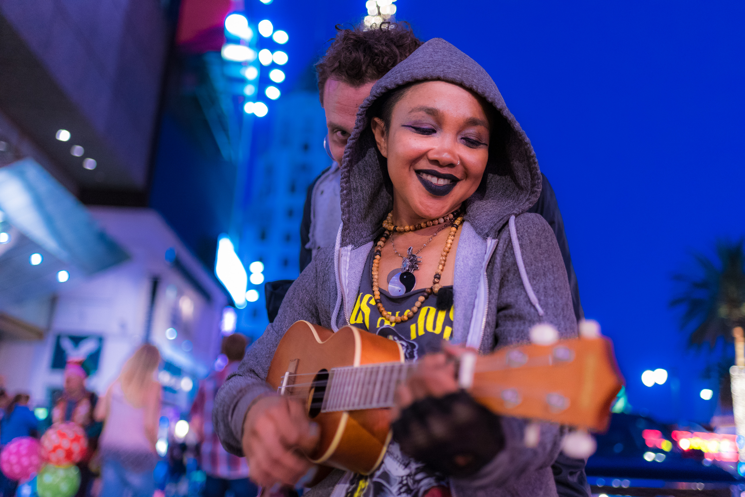 A woman in a hoodie plays a song in a ukulele as a guy behind her peeps around from behind