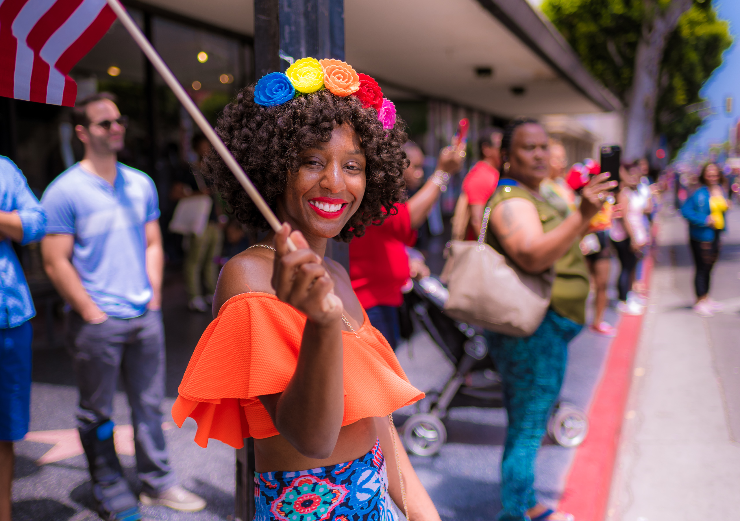 a woman watches the parade from the sidewalk. She has a rainbow assortment of flowers in her hair. She holds an American flag on a stick