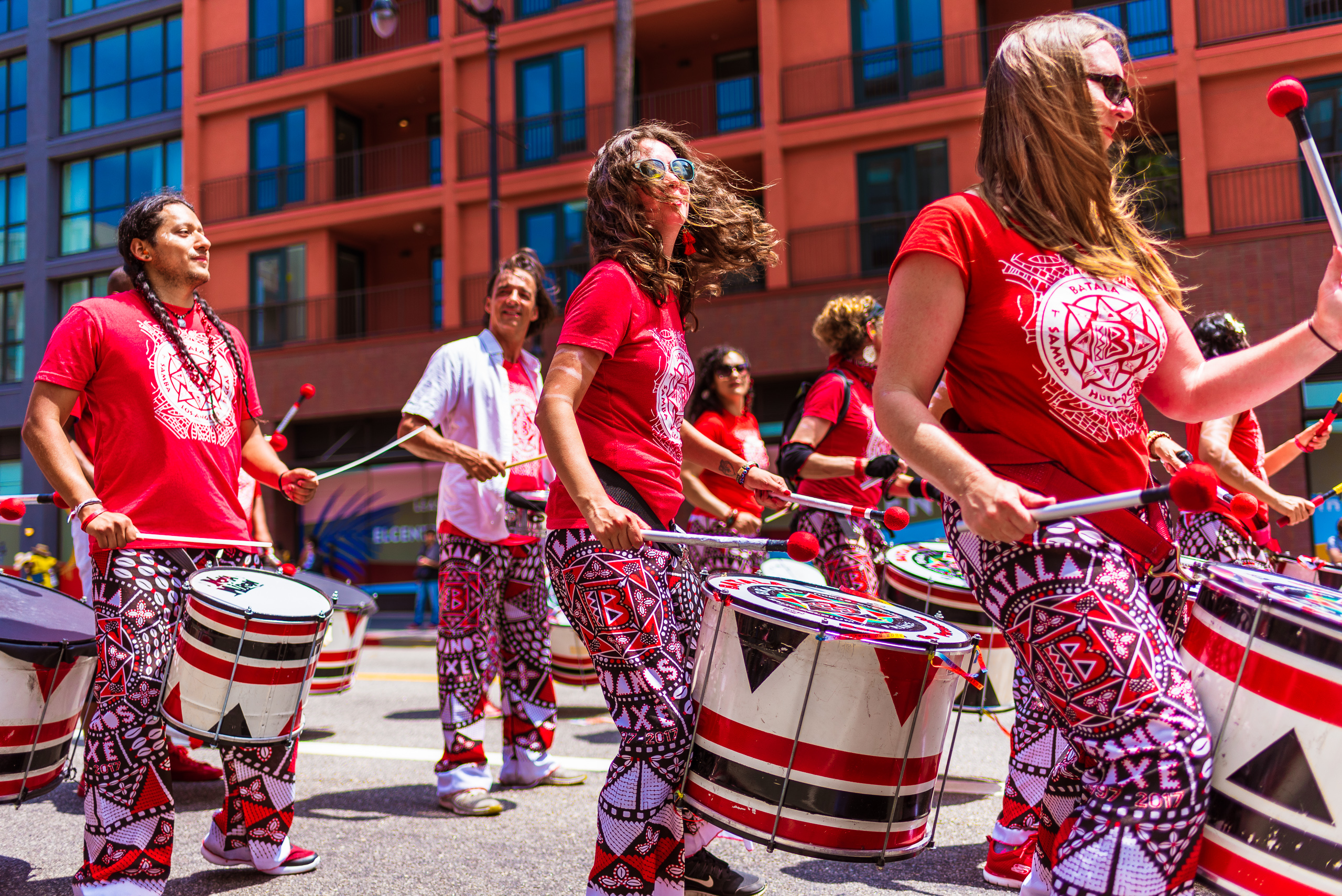 """Drummers from Batala Los Angeles and Batala Hollywood march down Hollywood Blvd in the Hollywood Carnival Parade. They wear red """"Batala Los Angeles"""" t-shirts and brightly colored pants in Red, Black, and White Batala Los Angeles patterns"""