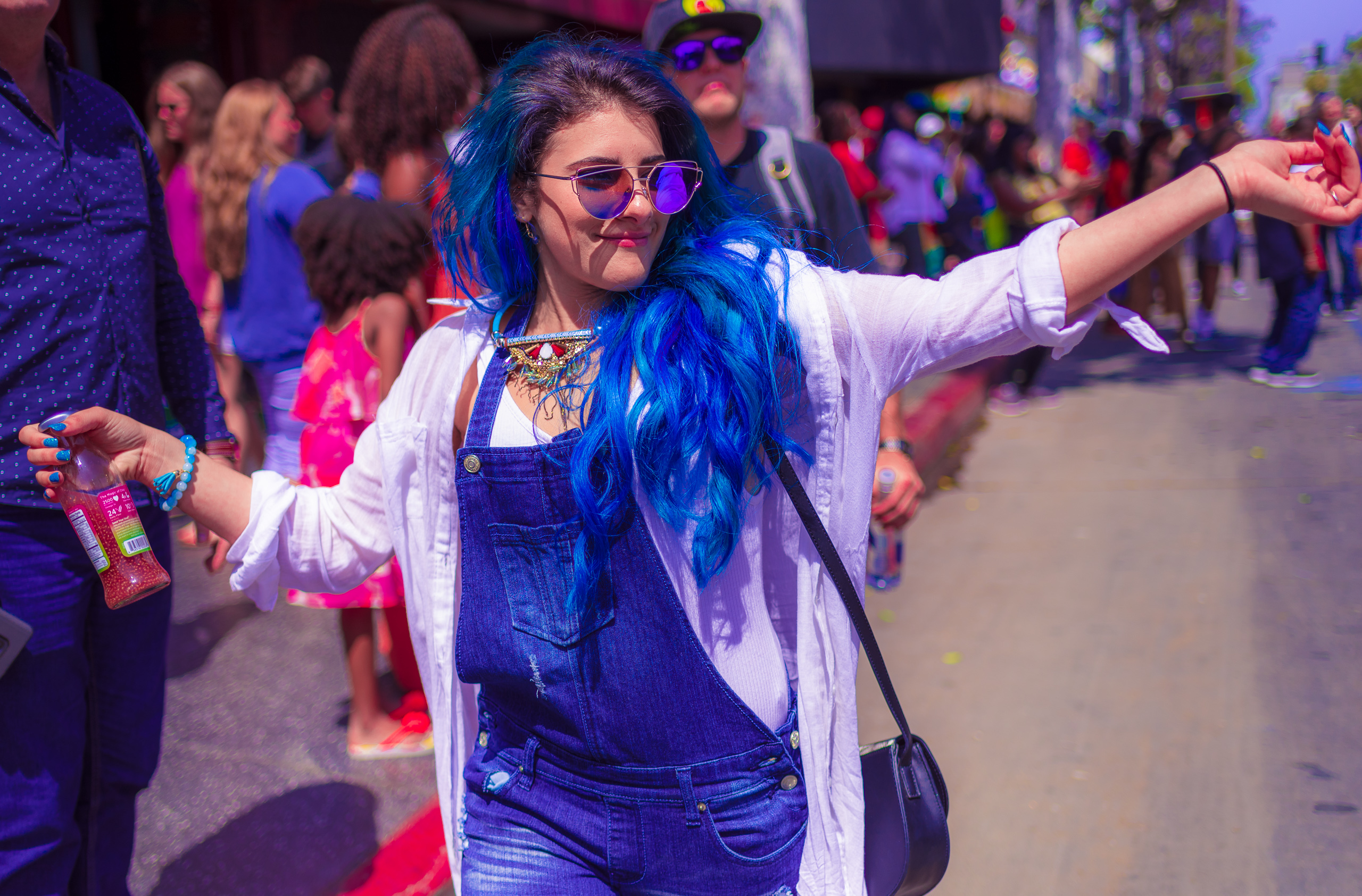 """a woman walks down Hollywood Blvd holding a bottle of Chia Drink, the label reads """"the magic of chia"""". The woman has blue hair, overalls, and nail polish. Her arms are extended in joy and she walks with a big smile on her face."""