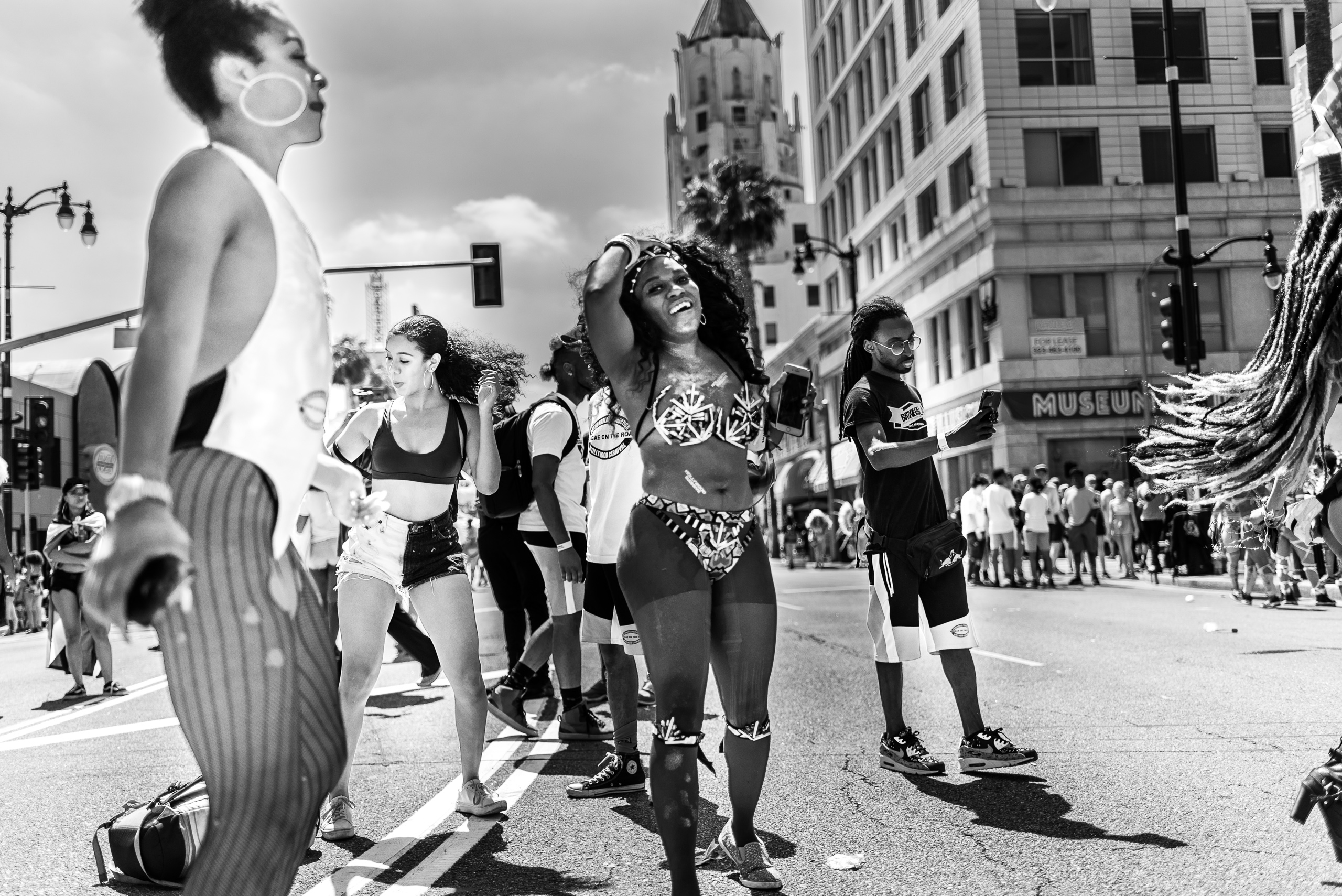 dancers from the 2018 Hollywood Carnival Parade stand, dance, and mill about in the center of the street on Hollywood Blvd