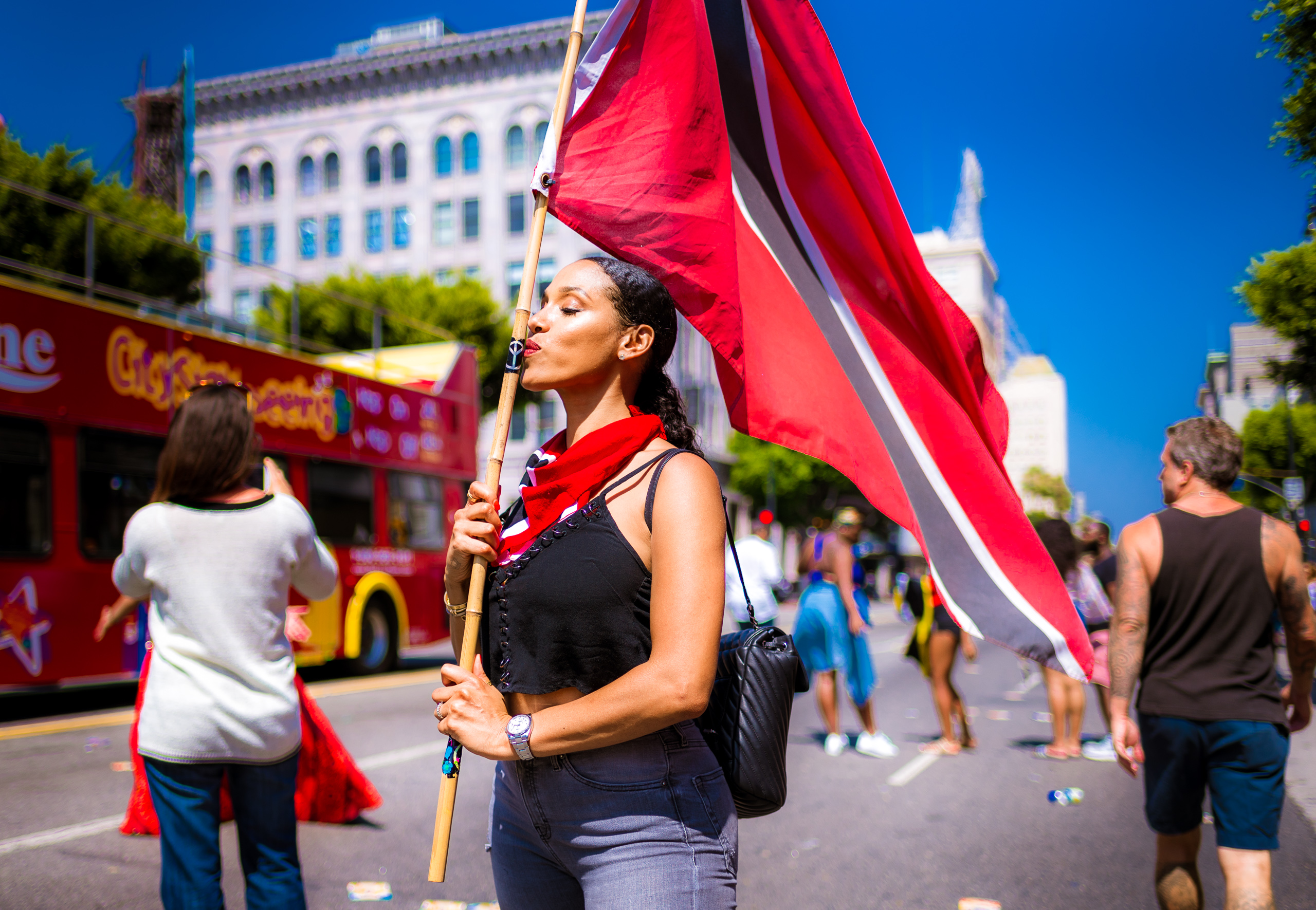 a woman on Hollywood Blvd holds a Trinidad & Tobago flag on a staff. Her eyes are closed as she kisses the staff.