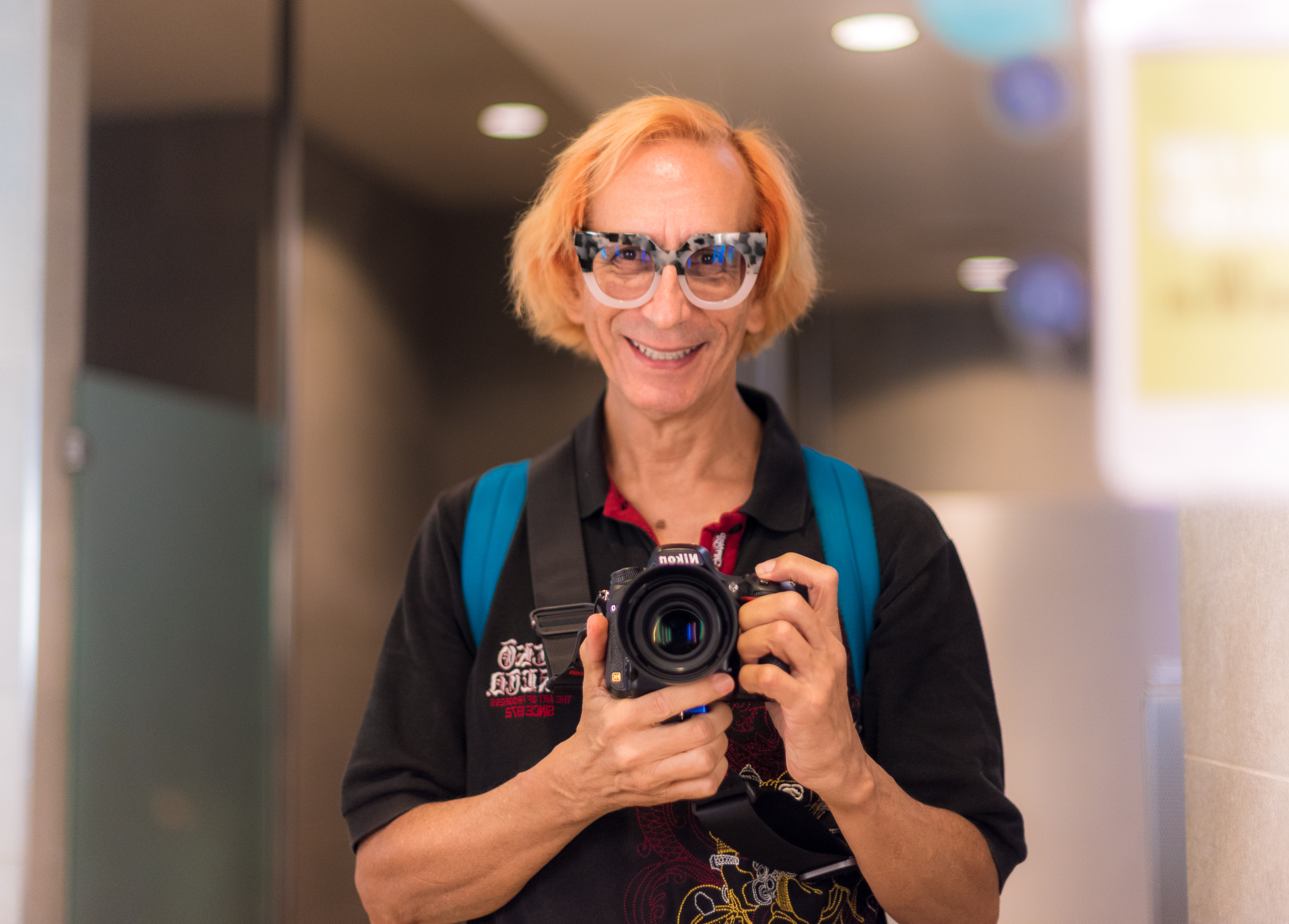 Glenn Zucman with blonde-red haircolor taking a Nikon D750 selfie in the food court men's room mirror