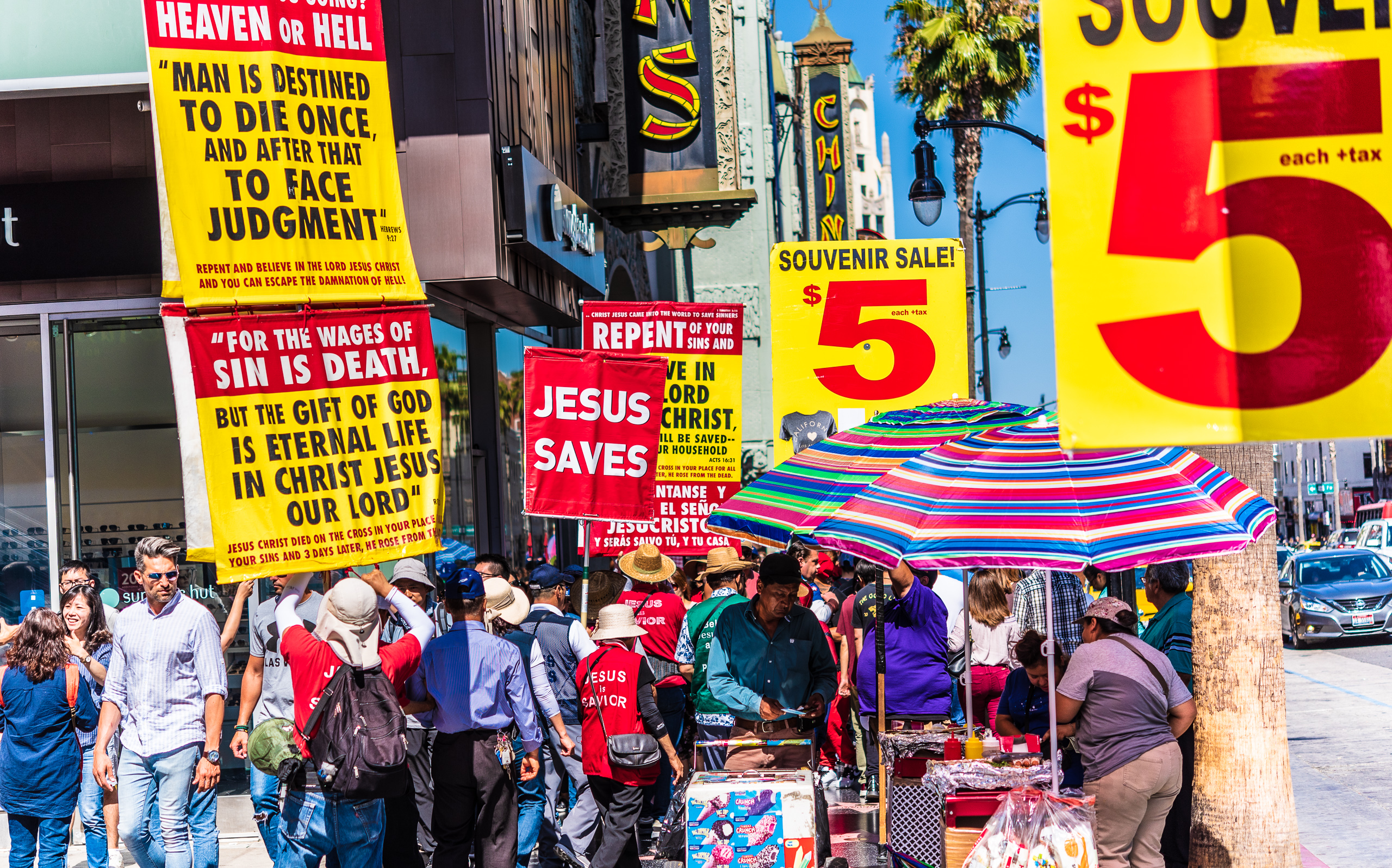 "a group of Asian Christians with many large banners, including one that reads ""Jesus Saves"", walk past several merchandise barkers with large ""$5"" banners. One of the ""Jesus Saves"" banners is adjacent to one of the ""$5"" banners, as if to read ""Jesus Saves Five Dollars"""
