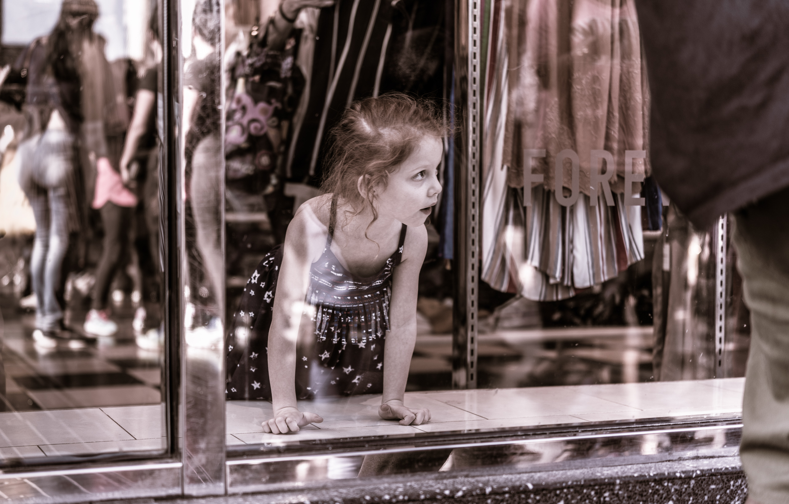 a young girl in the window display  inside Forever 21 at Hollywood & Highland looking out to the activity and people on the wide Hollywood Blvd sidewalk