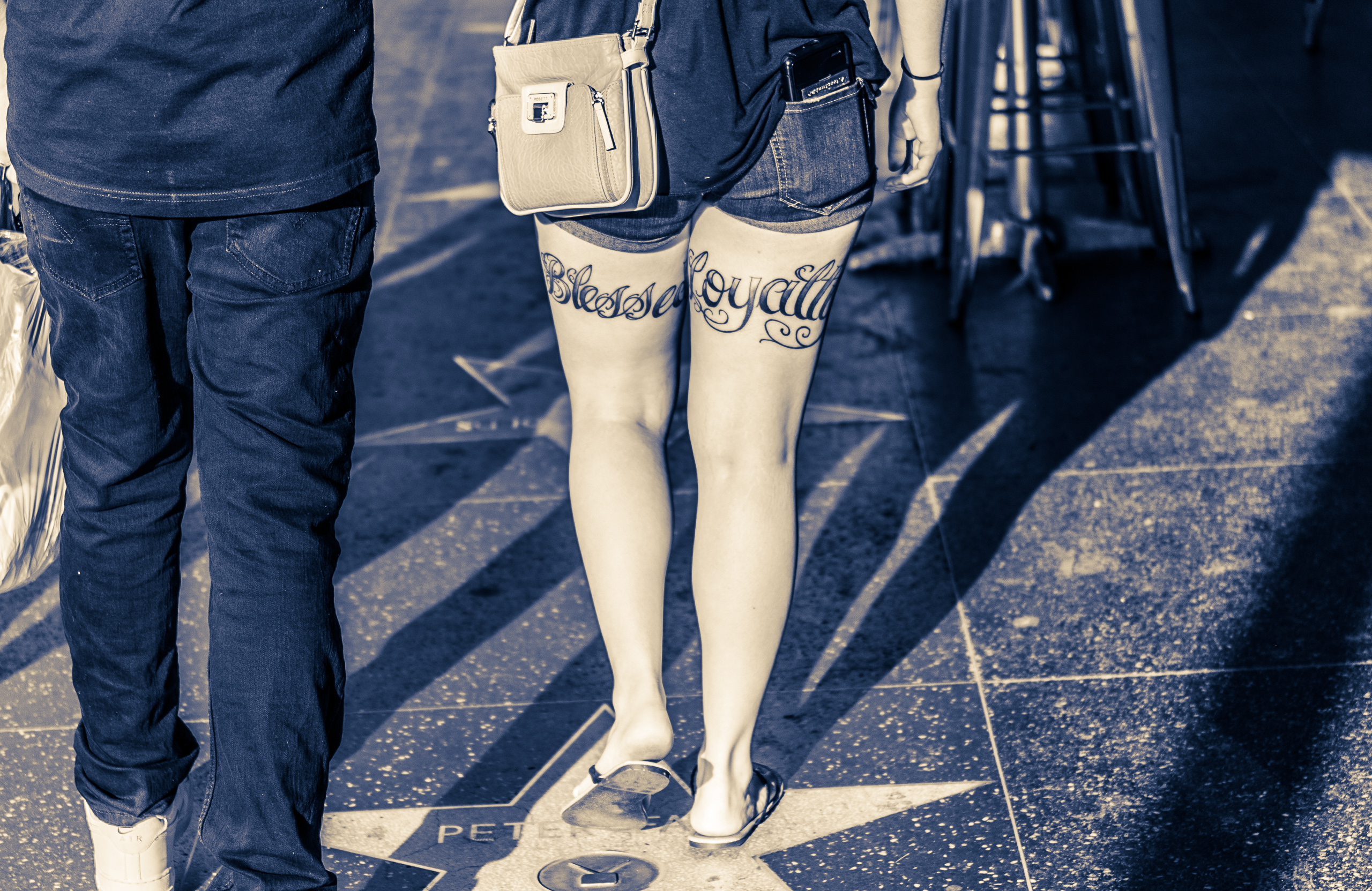 """a woman in denim shorts walks down Hollywood Blvd. Tattooed on the back of one thigh is the word """"Blessed"""" and on the back of her other thigh the word """"Loyalty"""" is tattooed"""