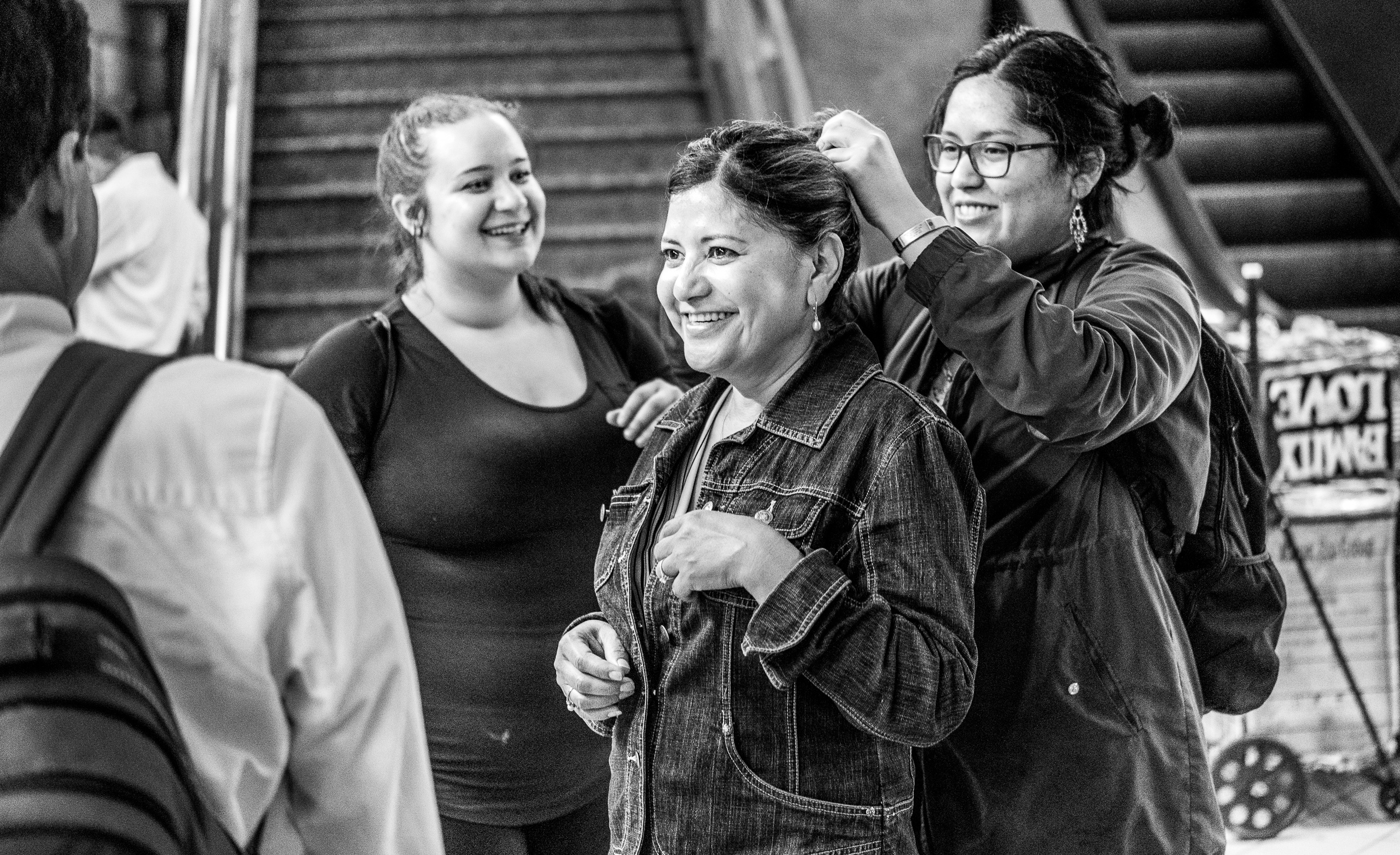 one woman puts another woman's hair up in a ponytail as 2 other friends look on and smile