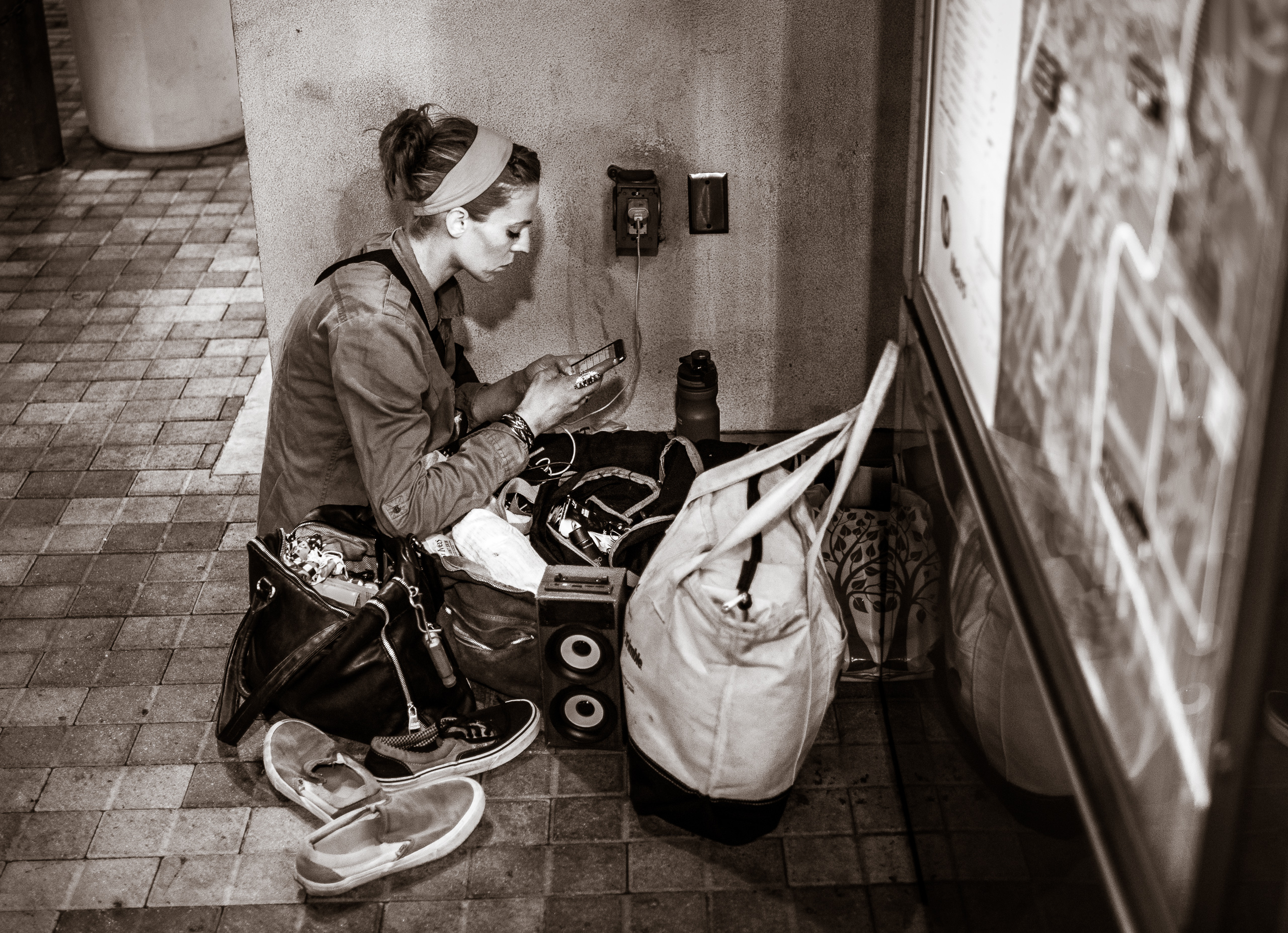 A Metro rider camps out at an electrical outlet on the Gold Line Platform at Union Station in Los Angeles. She has a couple of bags and checks her phone as it's plugged into an outlet