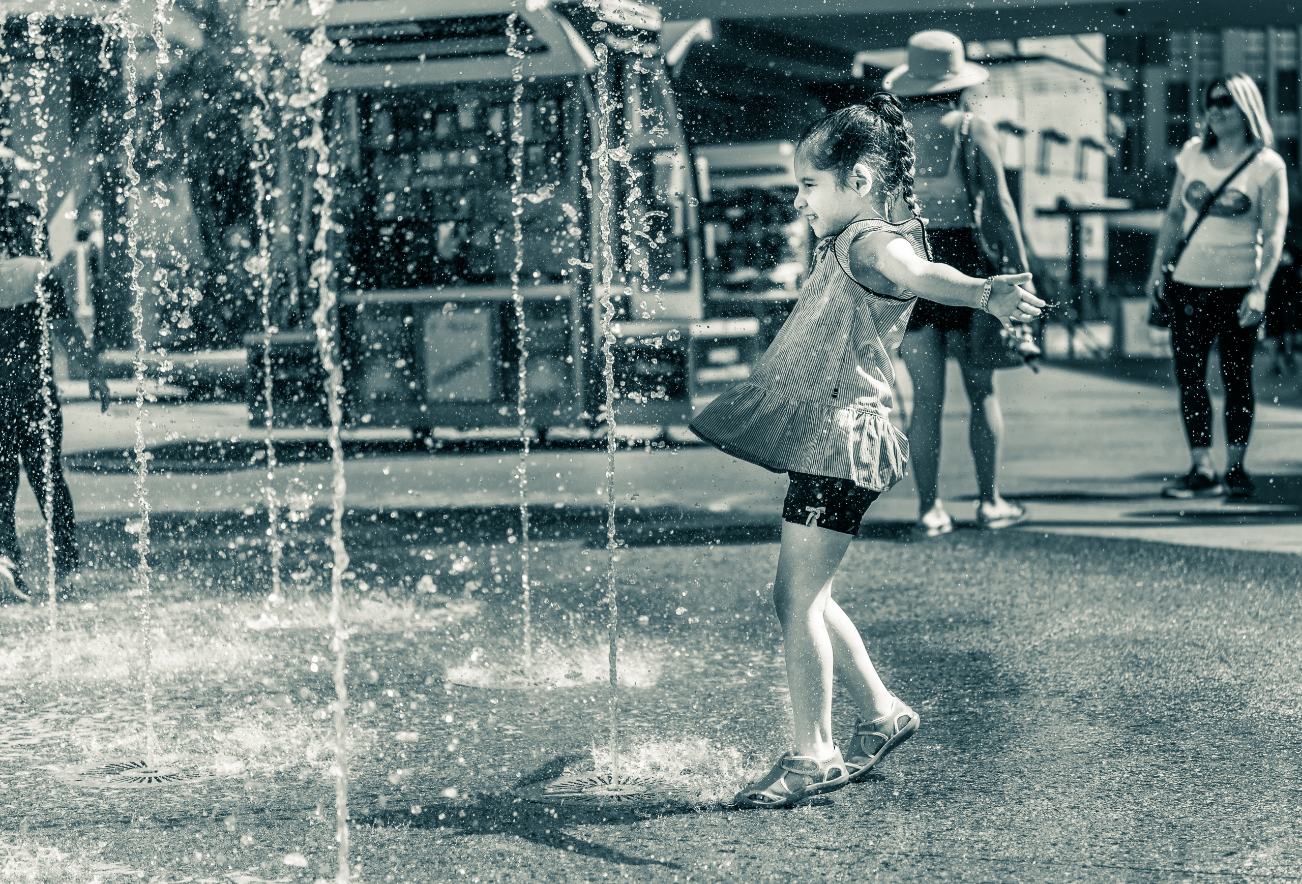 a young girl faces a vertical plume of water in the fountain at Hollywood & Highland Center on a really hot July day in Los Angeles
