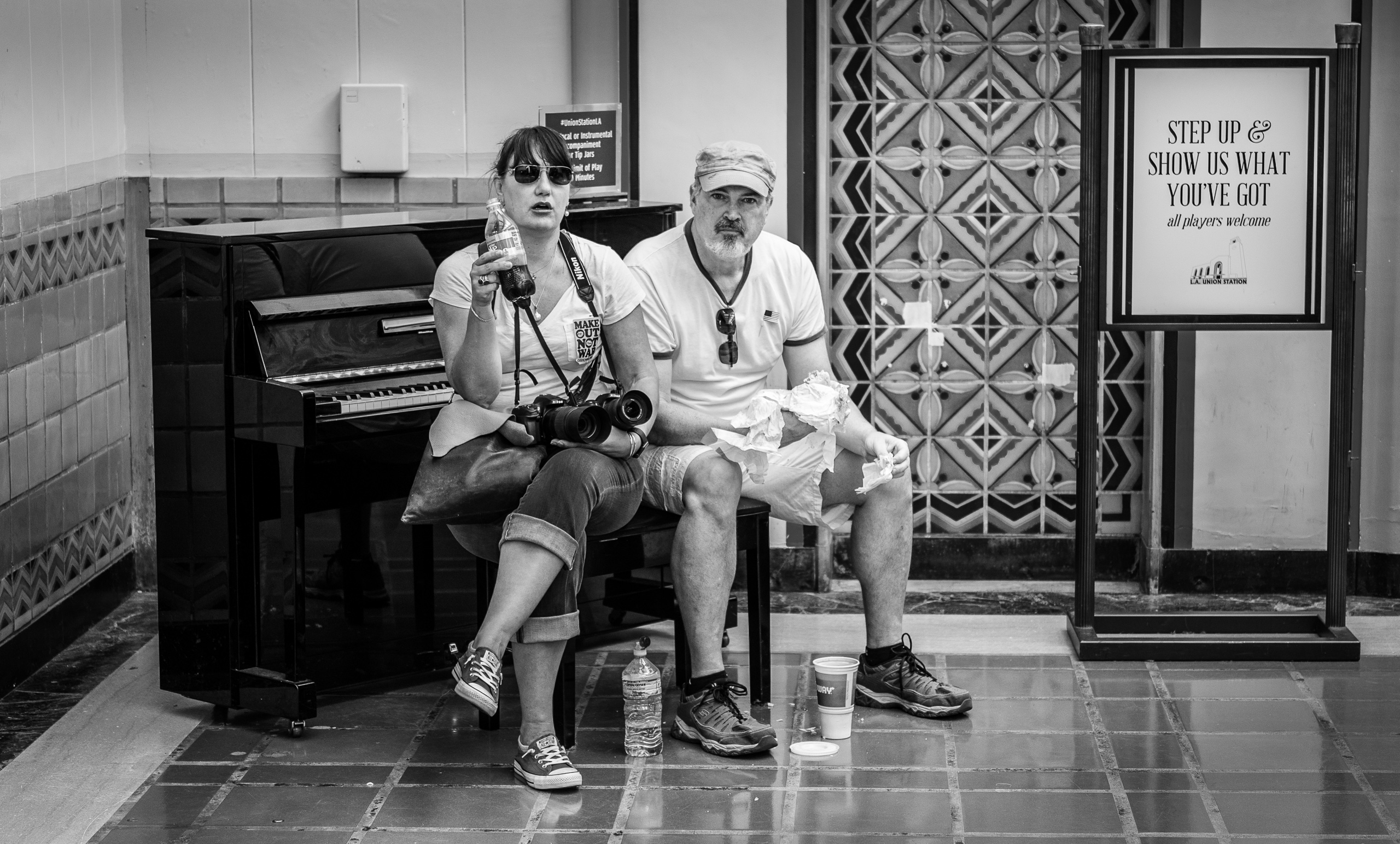 a couple sits on the piano bench at Union Station because they cannot find anyplace else to sit and eat the sandwiches they just bought at the Union Station Subway concession.
