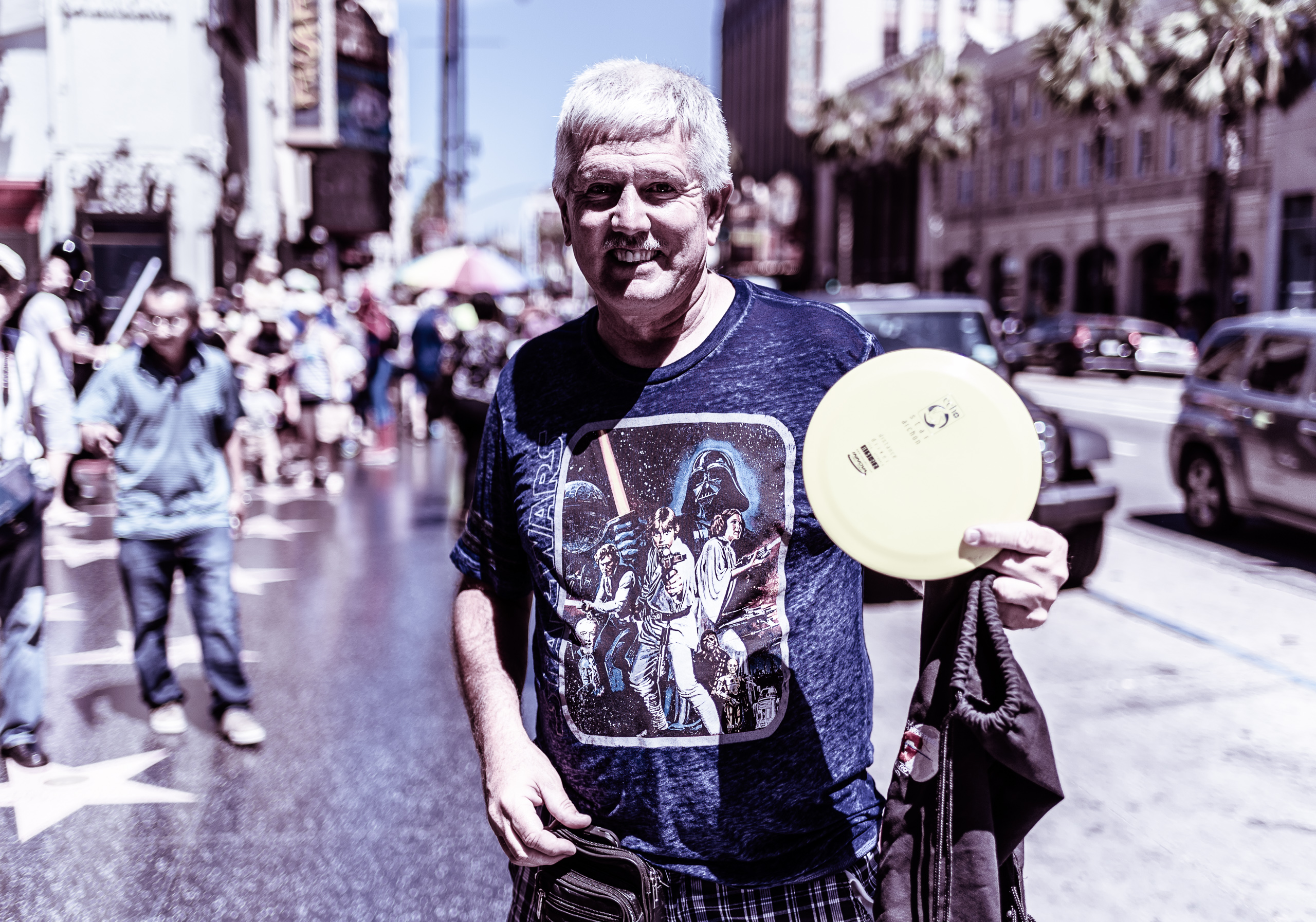 Larry Clifford Kirk, disc golf promoter, showing his disc (Frisbee) as he stands on the curb on Hollywood Blvd