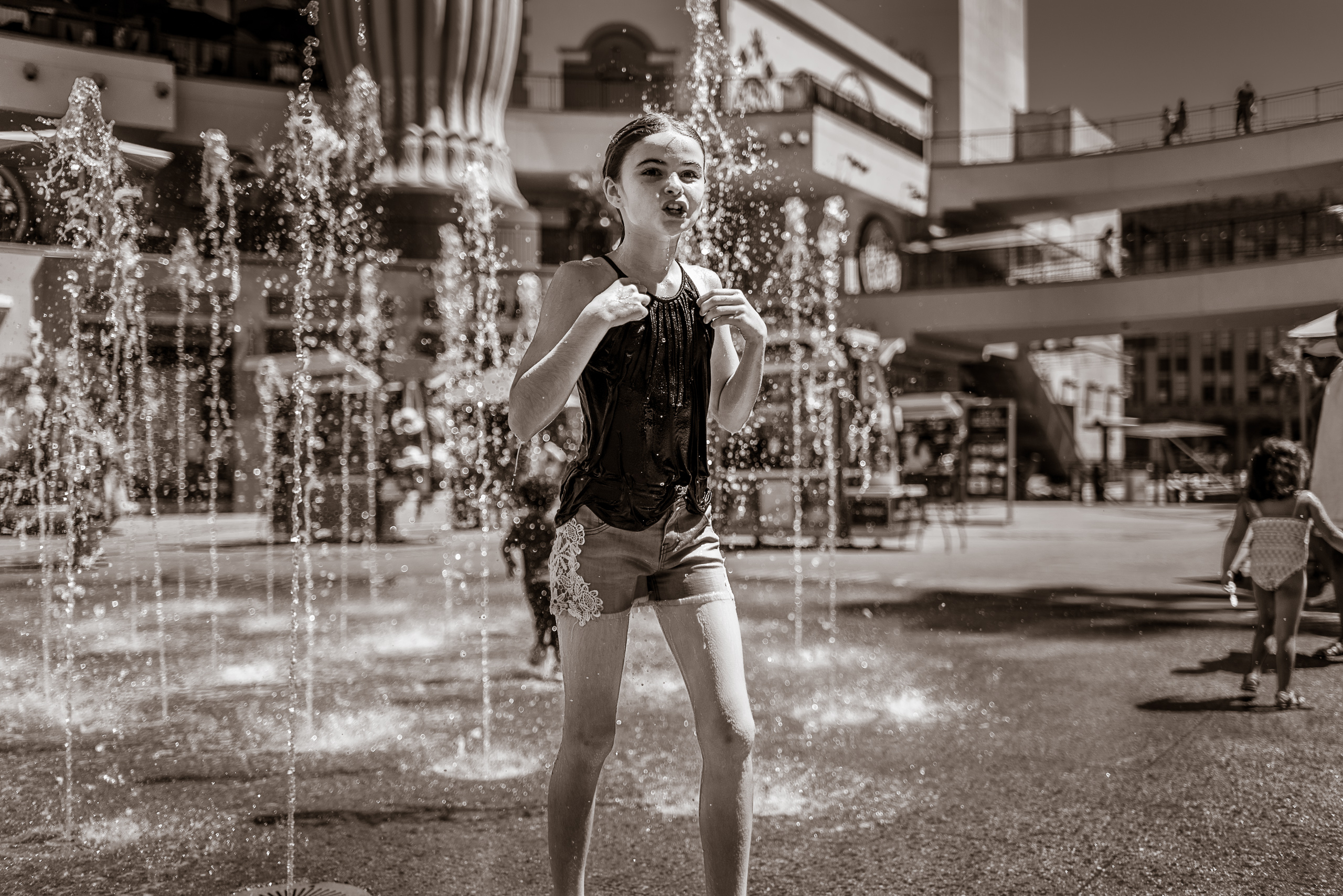 a girls is soaked, and happy, in the fountain at Hollywood & Highland on a hot summer day
