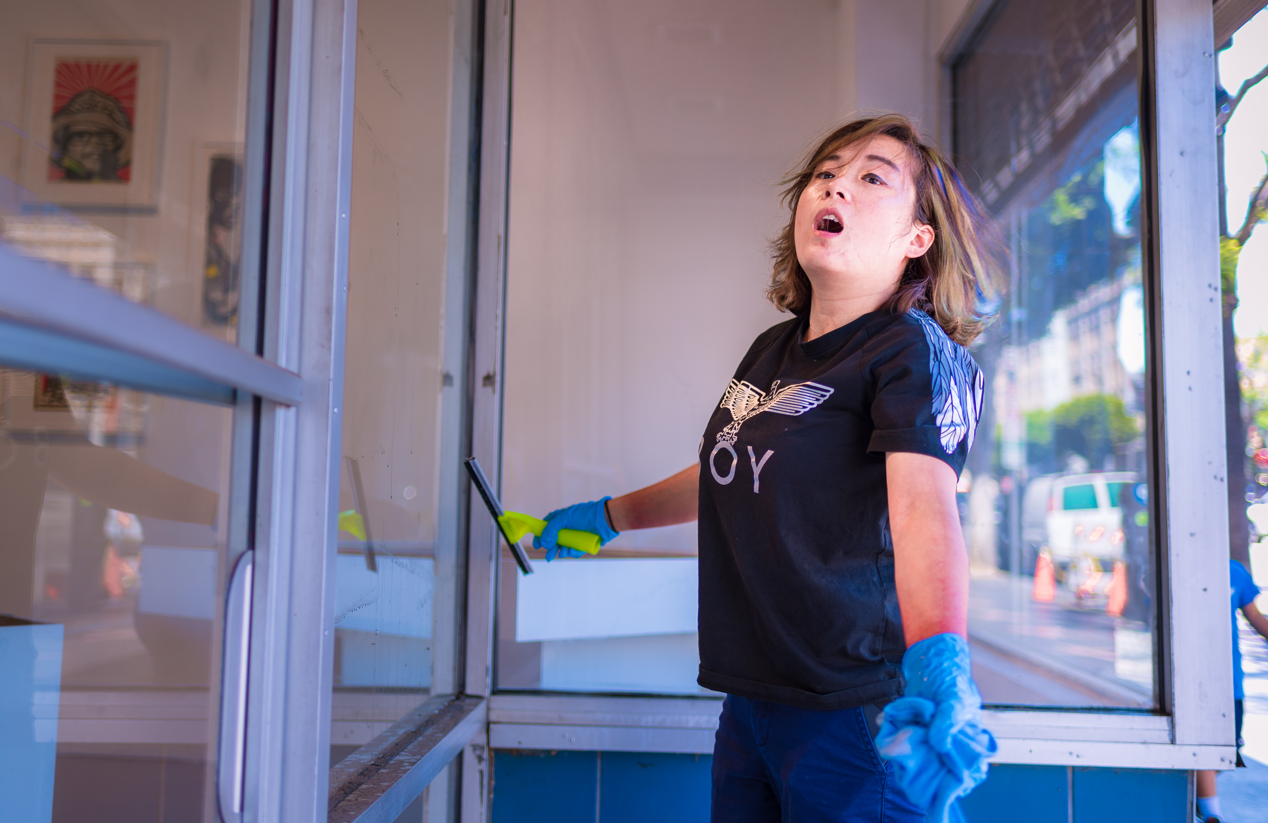 a LACE staff member wearing blue rubber gloves and holding a squeegee in one hand surveys the LACE storefront windows she is cleaning