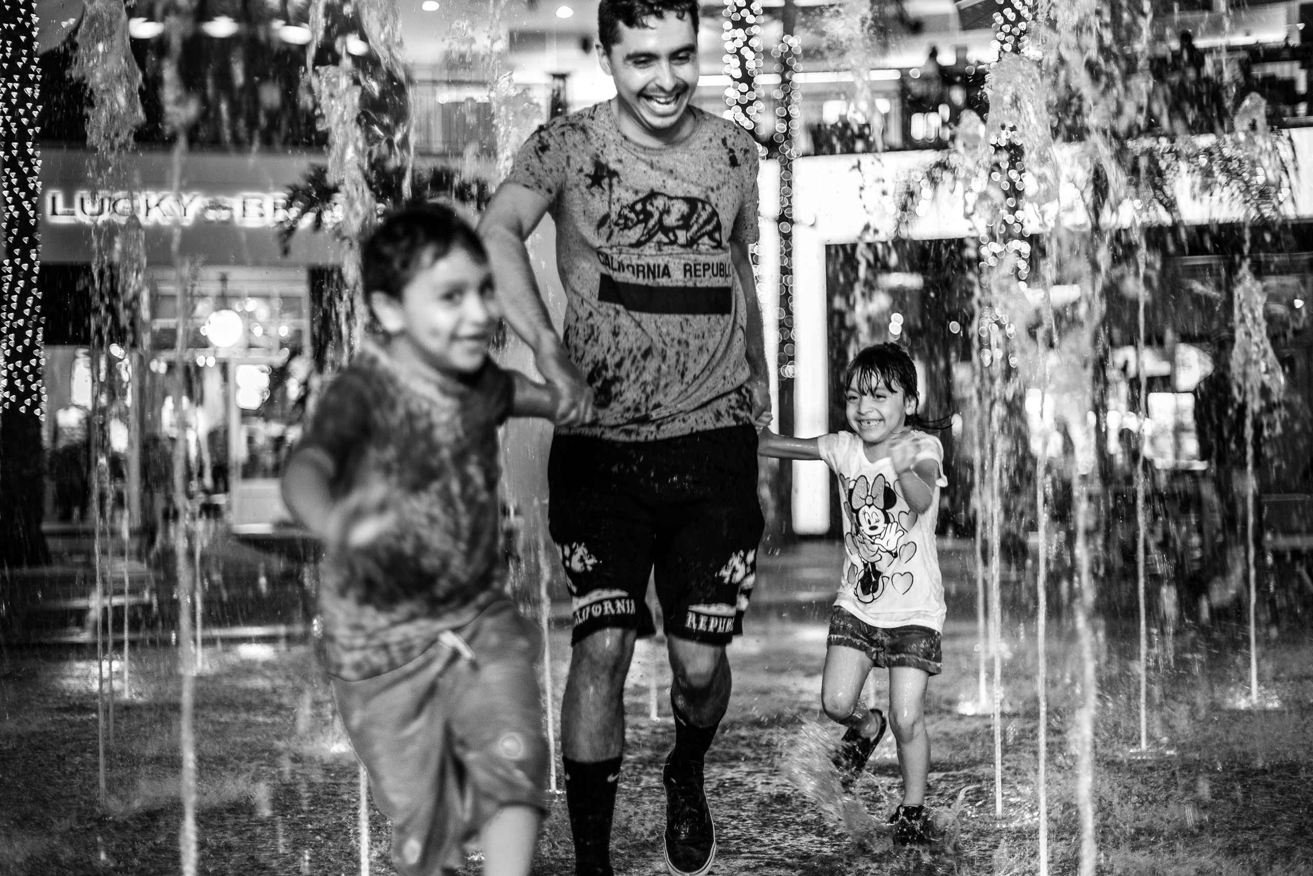 a father holds the hands of his young son and daughter as the 3 of them dash through the fountain in the center of the Hollywood & Highland shopping center in Los Angeles, California