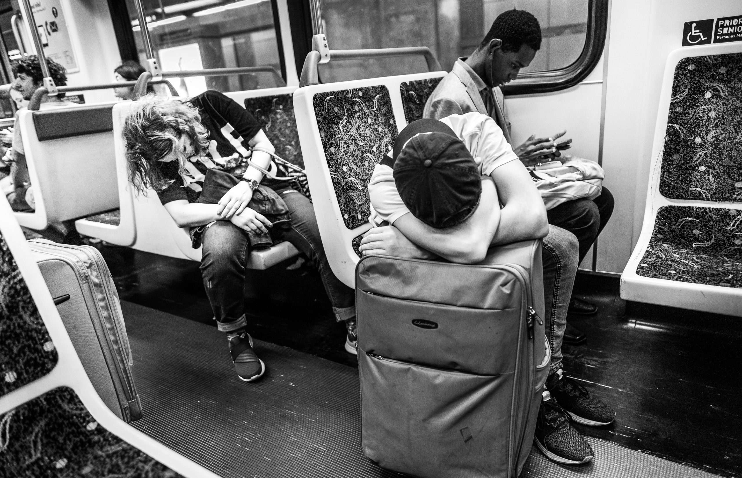 black-and-white photo of riders on an LA Metro Red Line train car sleeping