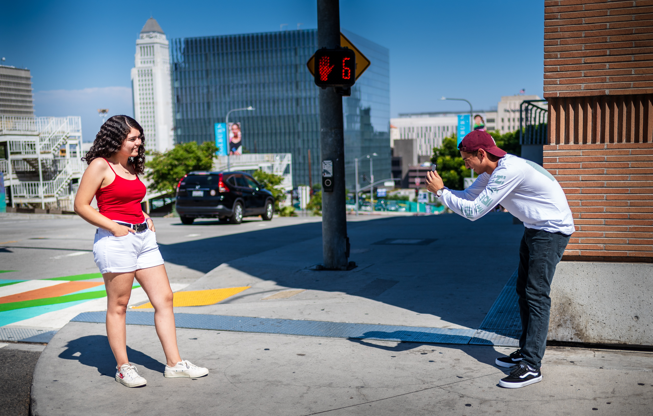 a guy taking a street portrait of his girlfriend on Grand Avenue in Los Angeles with LA City Hall in  the background