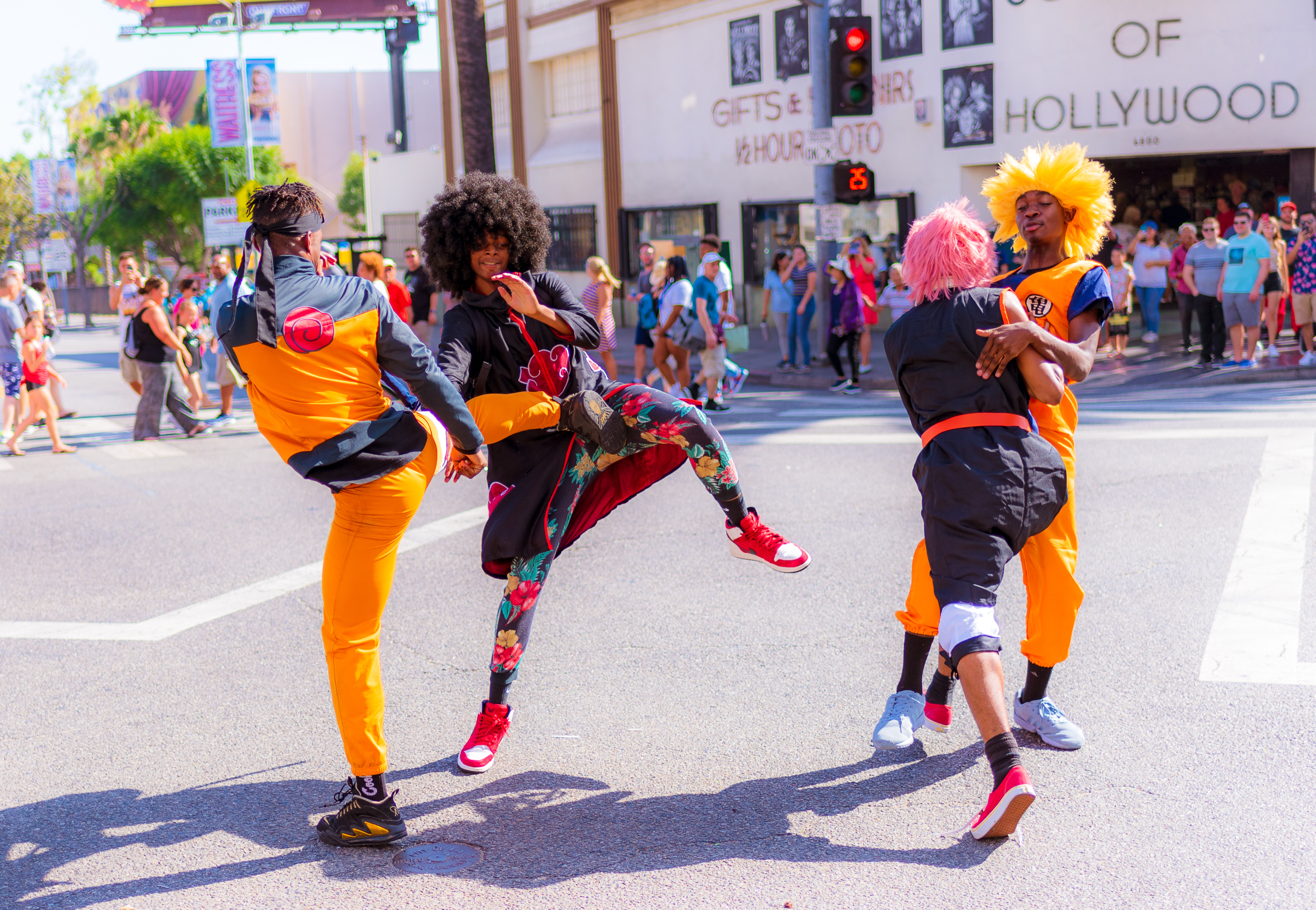 4 people in colorful costumes and BIG hair wigs stage a fight in the middle of the 4-Way crossing at Hollywood & Highland