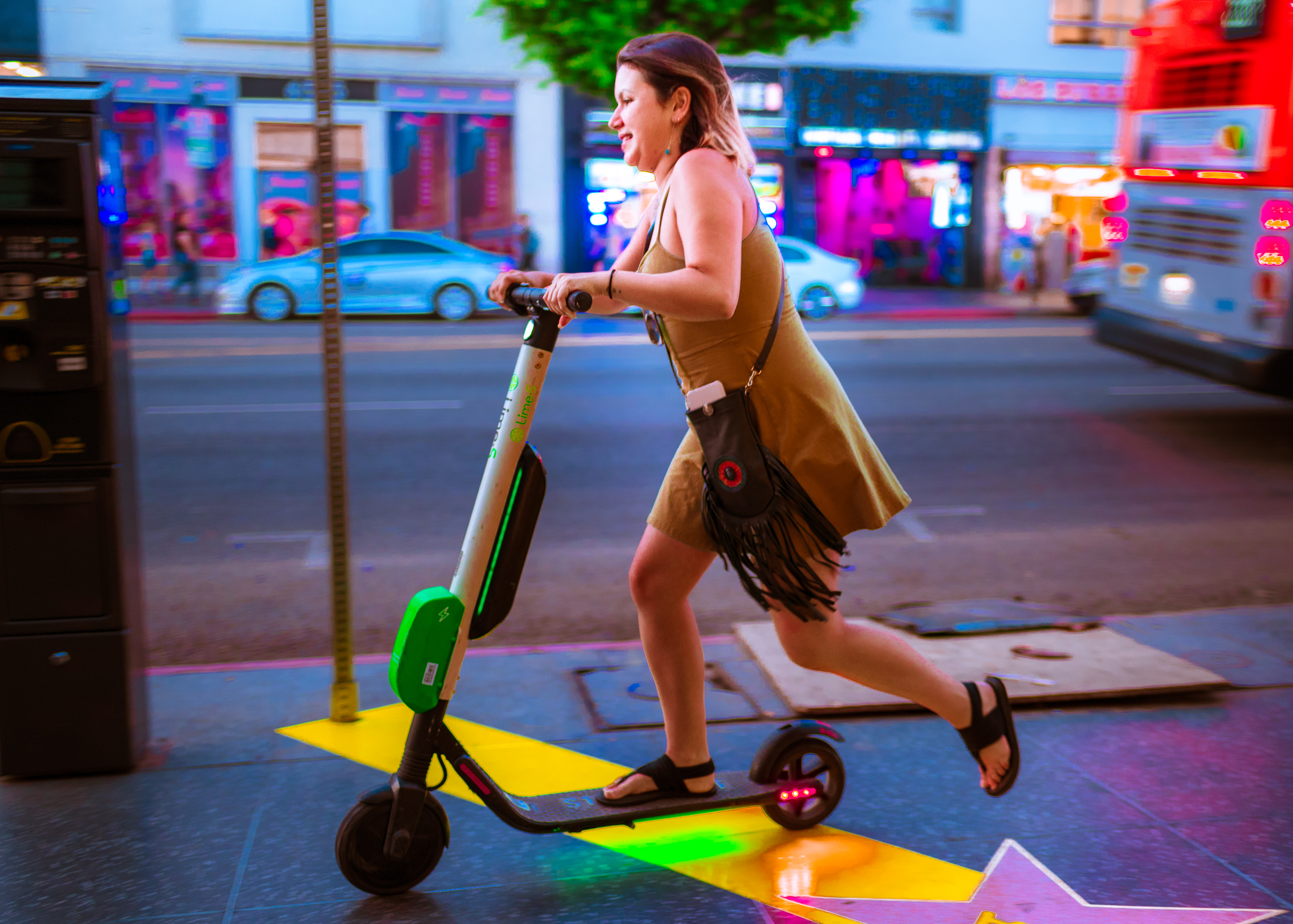 a woman rides a Lime-s electric scooter down Hollywood Blvd. I'm not sure if the charge was low, but for whatever reason, she's giving in a foot kick as if it were a non-powered scooter
