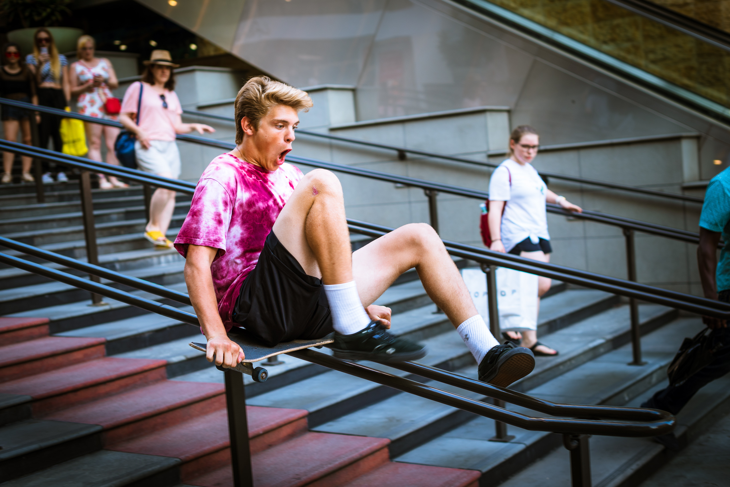 a young guy in a tie-dye t-shirt rides a skateboard sideways as it slides down the railing at the steps in front of Hollywood & Highland