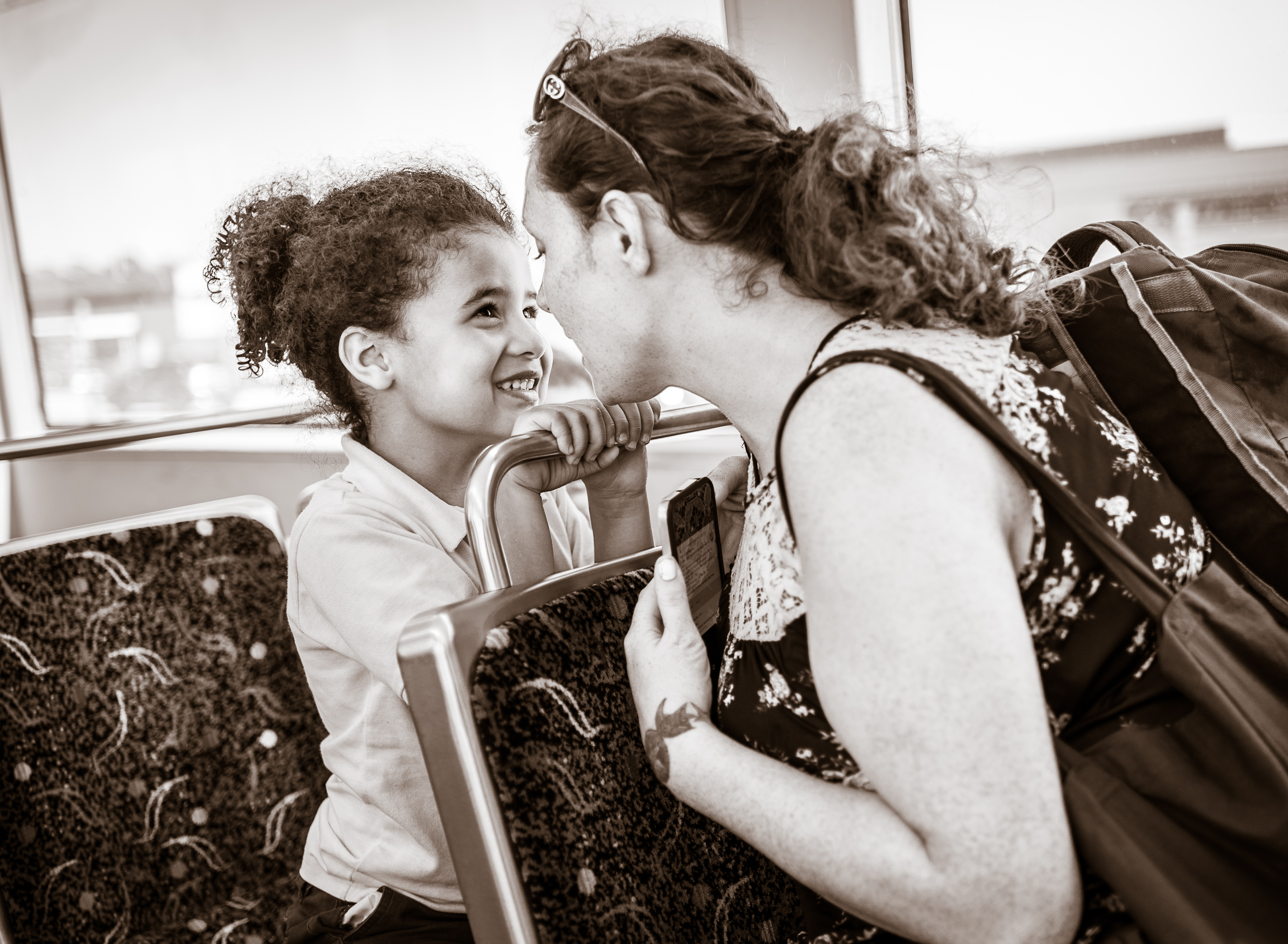 a mother and daughter riding the LA Metro's Green Line. Mom sits one seat in front and turns back toward her daughter. The girl's tiny hands hold the rail on the seat back as she stares lovingly into her mother's eyes
