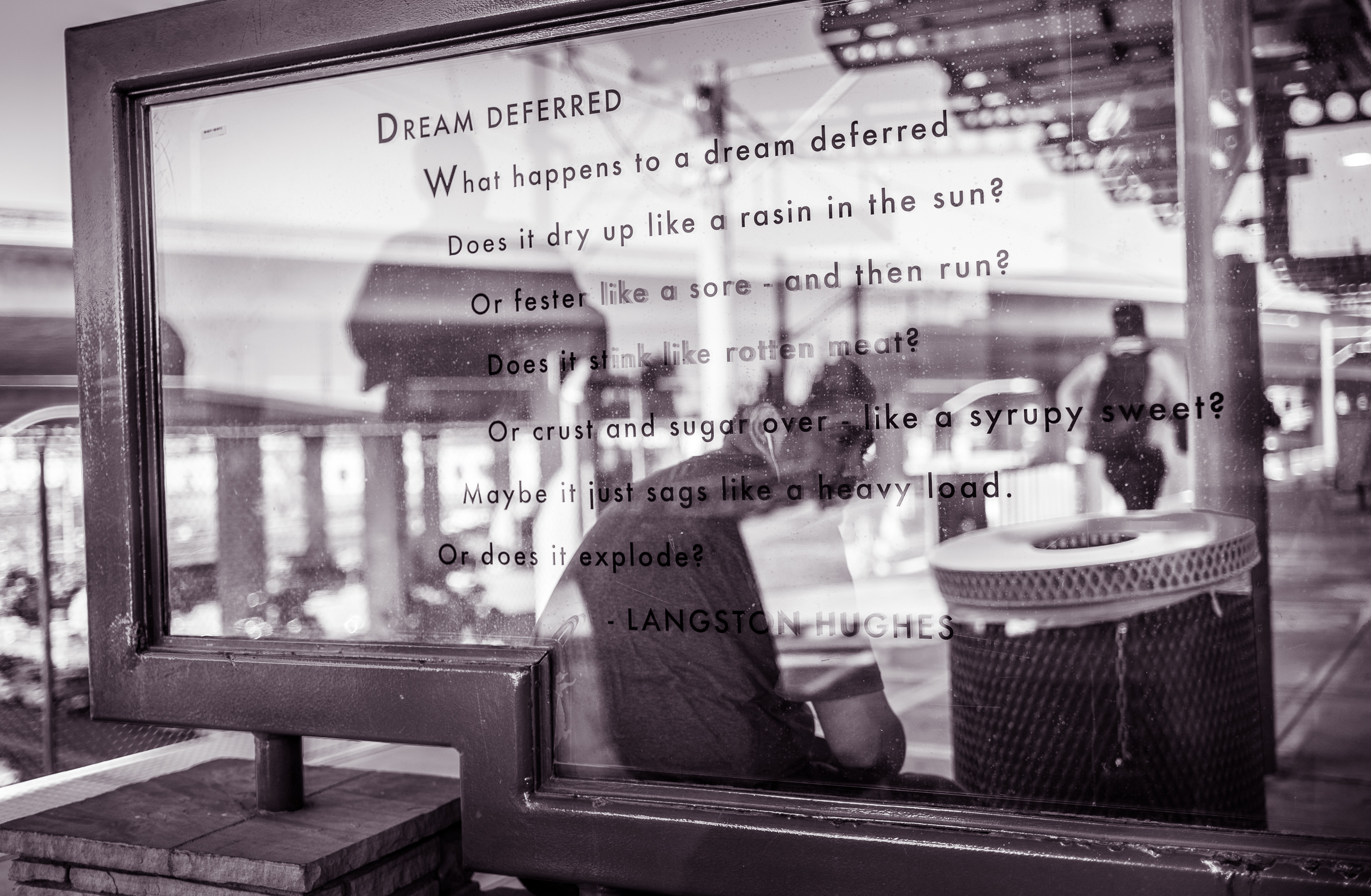 "at the Aviation/LAX Station platform on the LA Metro Green line, Langston Hughes' poem ""Dream Deferred"" is written on a glass panel. A man sits in a quiet moment on the other side of the glass"