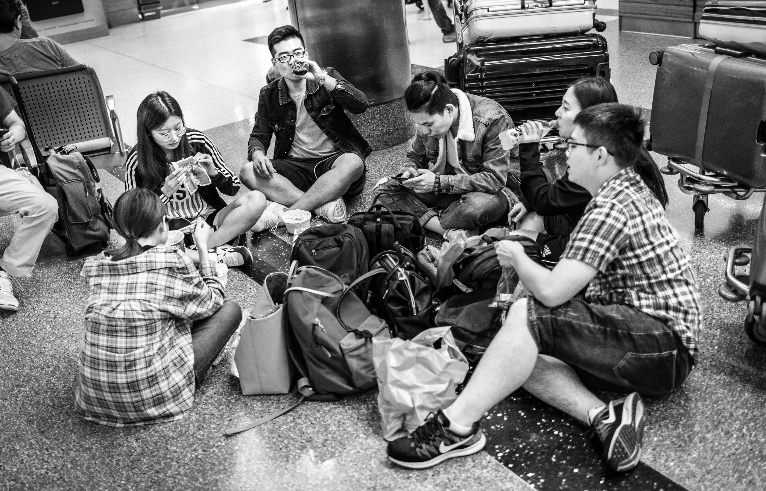 a group of travelers sits in a floor circle at the Tom Bradley International Terminal at LAX. They share food, drink, and conversation.