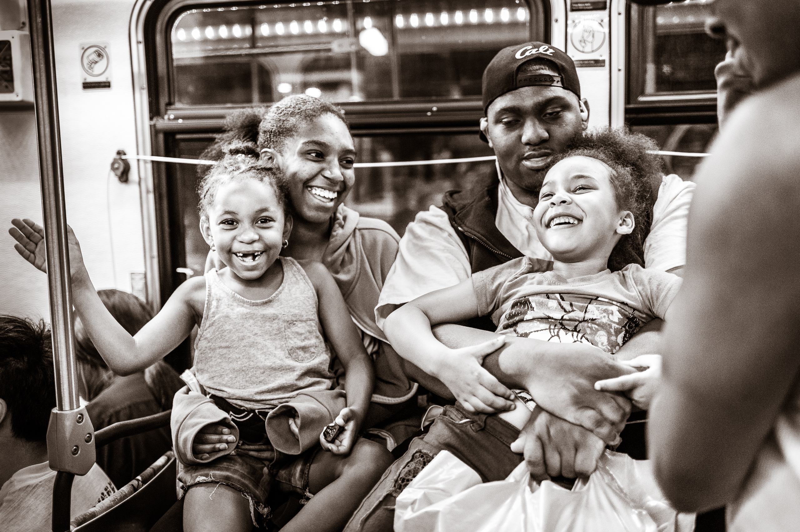 two kids and two adults riding the Blue Line in happy conversation