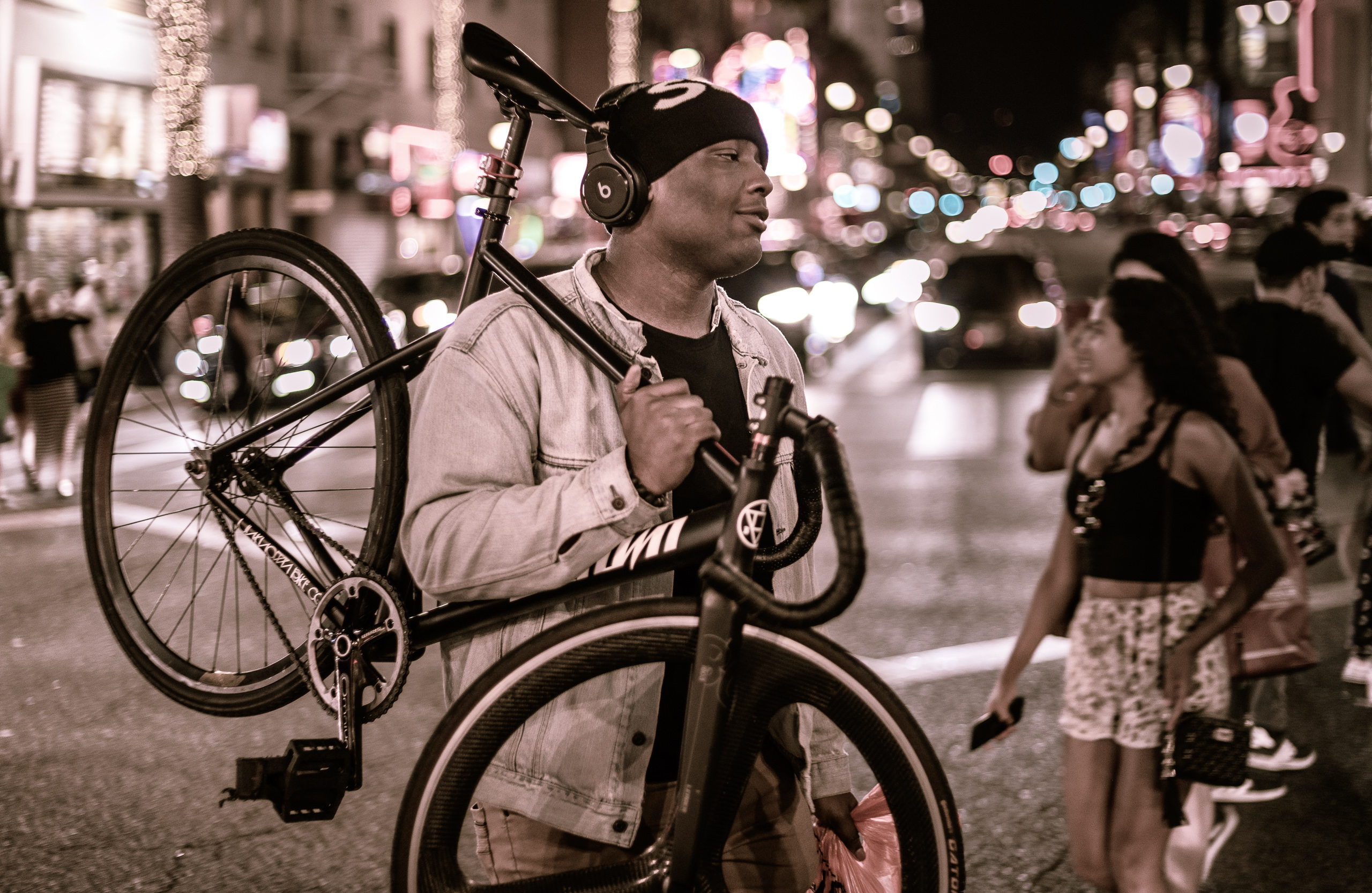 a guy carries his Unknown Bike Co fixed-gear bicycle across the intersection at Hollywood & Highland