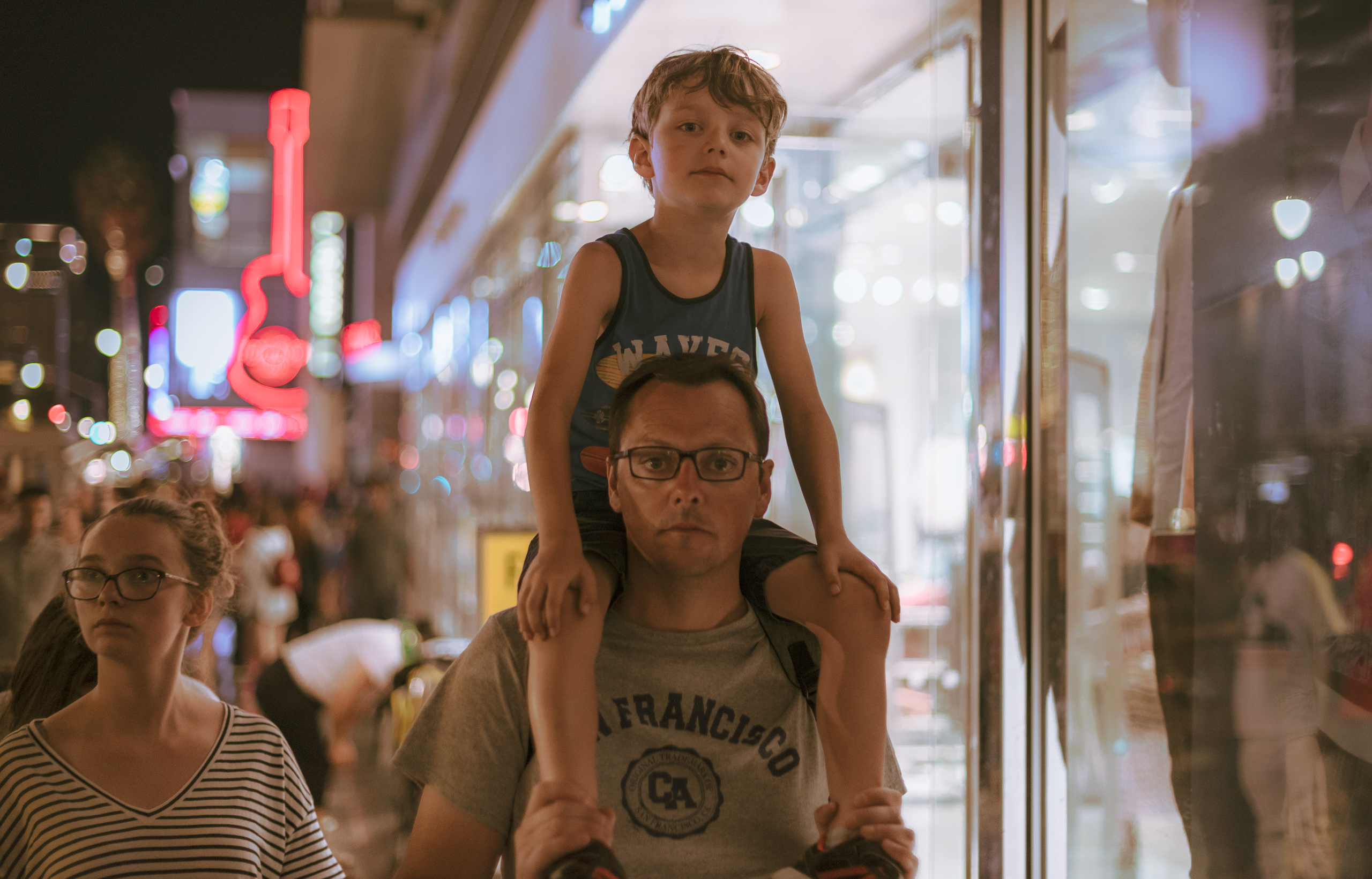 a man carries his young son on his shoulders as they walk past the Forever 21 at Hollywood & Highland