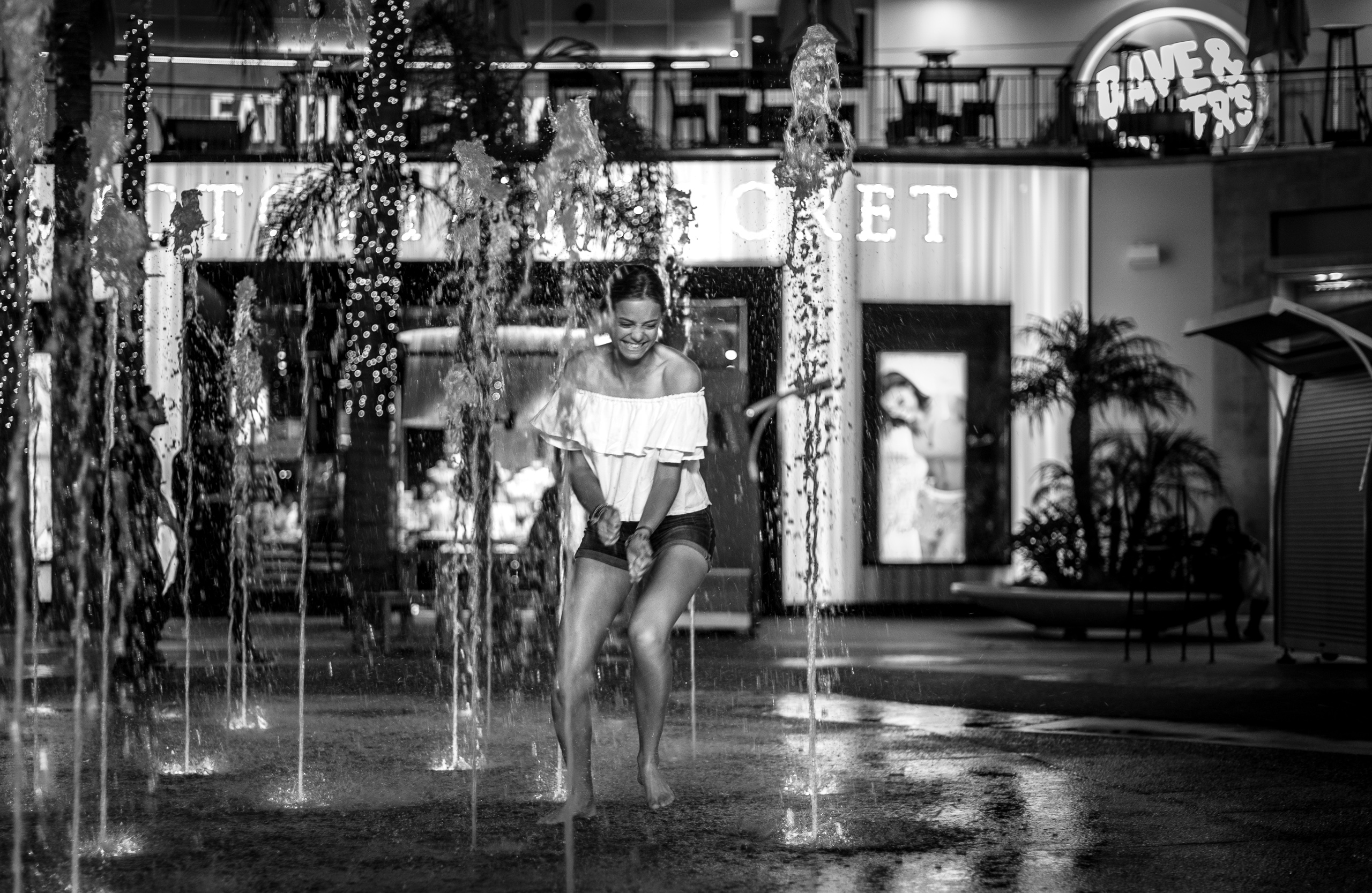 a woman takes her shoes off to run through the center of the fountain at the Hollywood & Highland shopping center on a hot summer night in Los Angeles