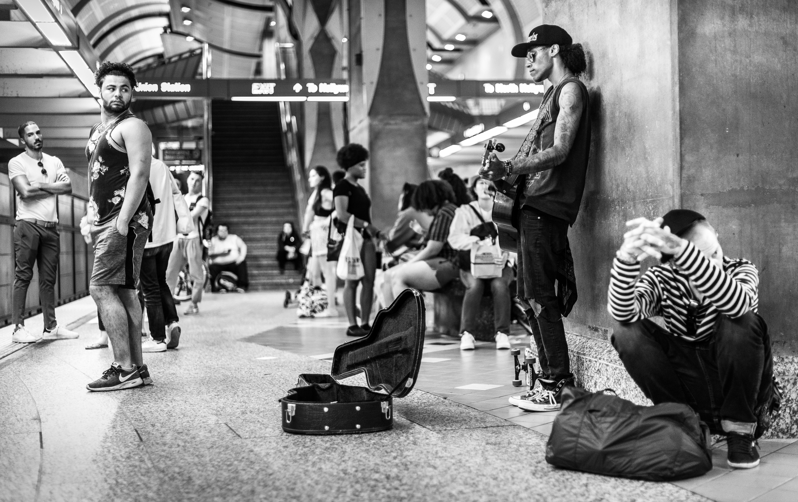 a guy plays guitar as he waits on the Red Line platform at Hollywood & highland