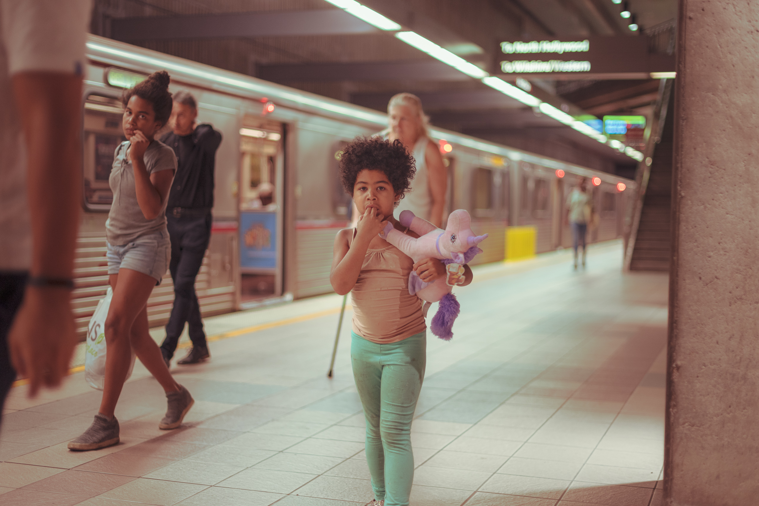 a young girl clutches a unicorn plush animal as she walks through the Red Line terminal at Union Station at night