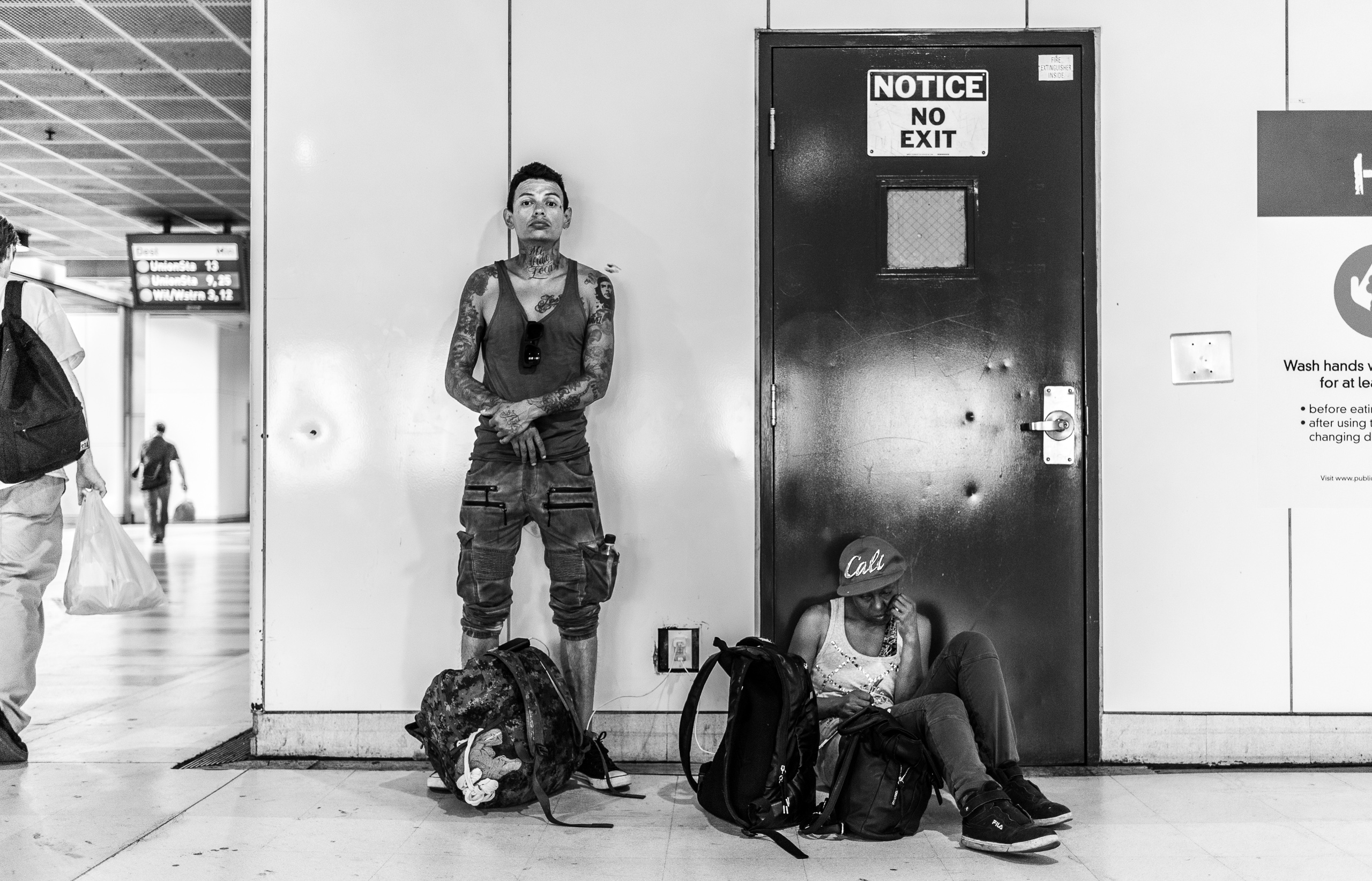 "two people use an electrical outlet at the Pershing Square station of the LA Metro Red Line. One sits in front of a door that bears a sign ""Notice, No Exit"""