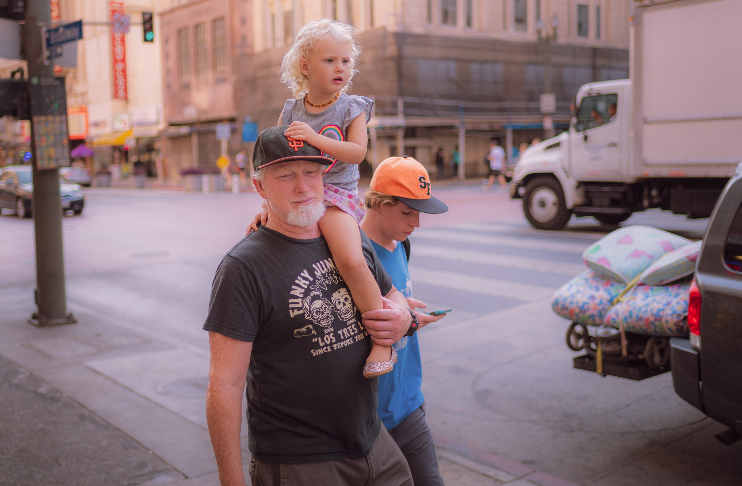 a man walks down Broadway with his young daughter on his shoulder