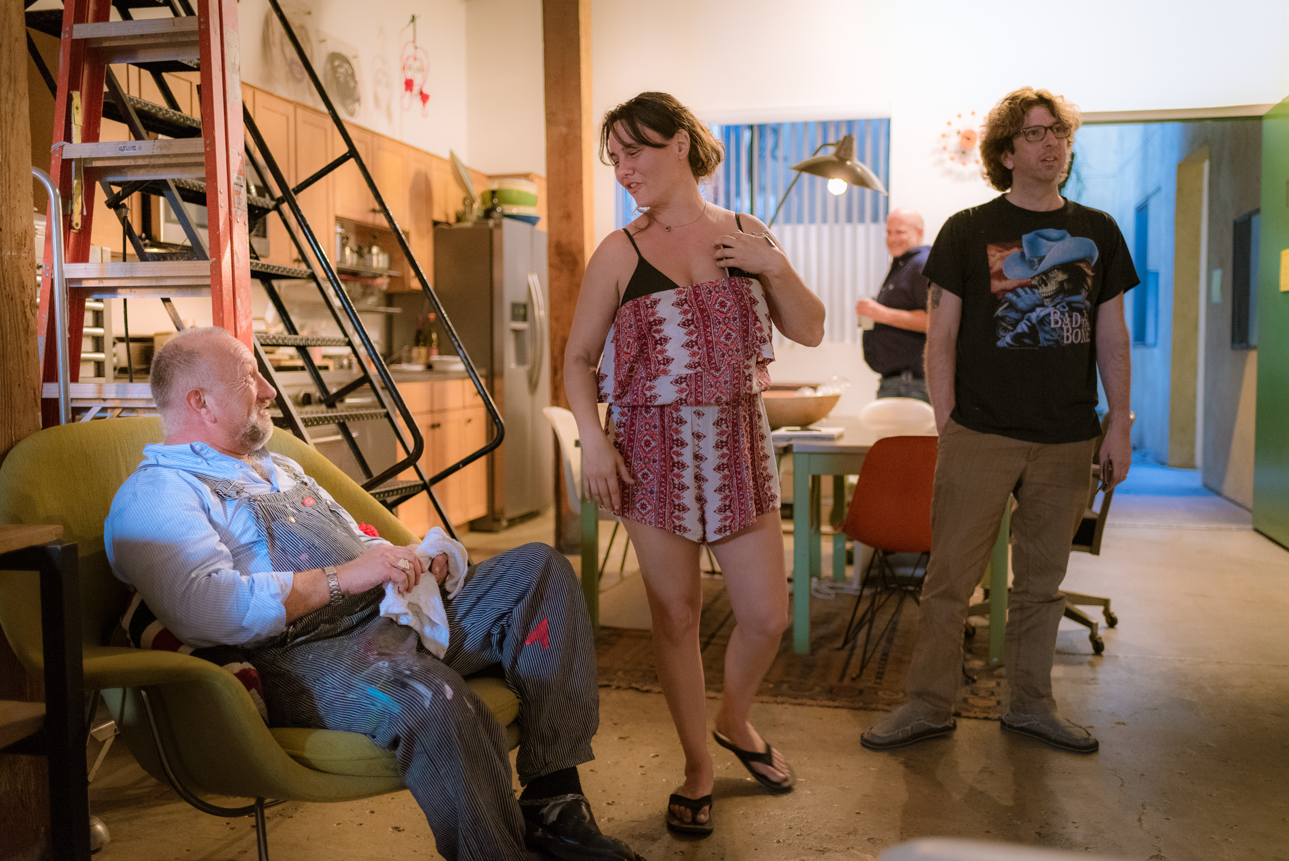 """Long Beach Avenue Lofts resident """"ST"""" sits in a chair in his studio, #113, and discusses his work with visitors to the artwalk"""