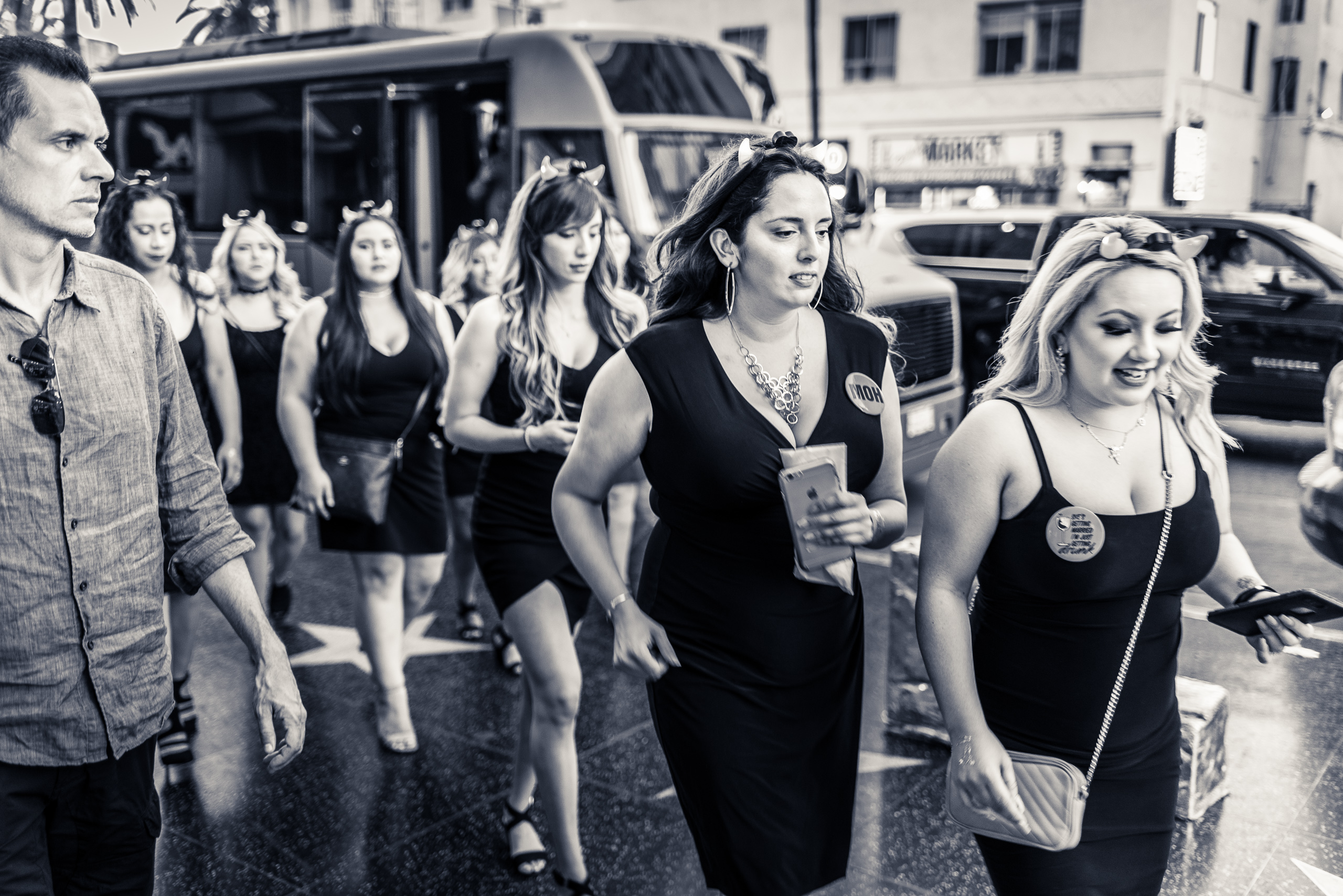 "a group of women get off a shuttle bus and head for a bridal shower at the Hollywood & Highland center in Los Angeles. They all wear little black dresses and horns on their heads. The first one wears a button that reads ""She's getting married, I'm just getting drunk"" and the second woman wears a button that reads ""MOH"""