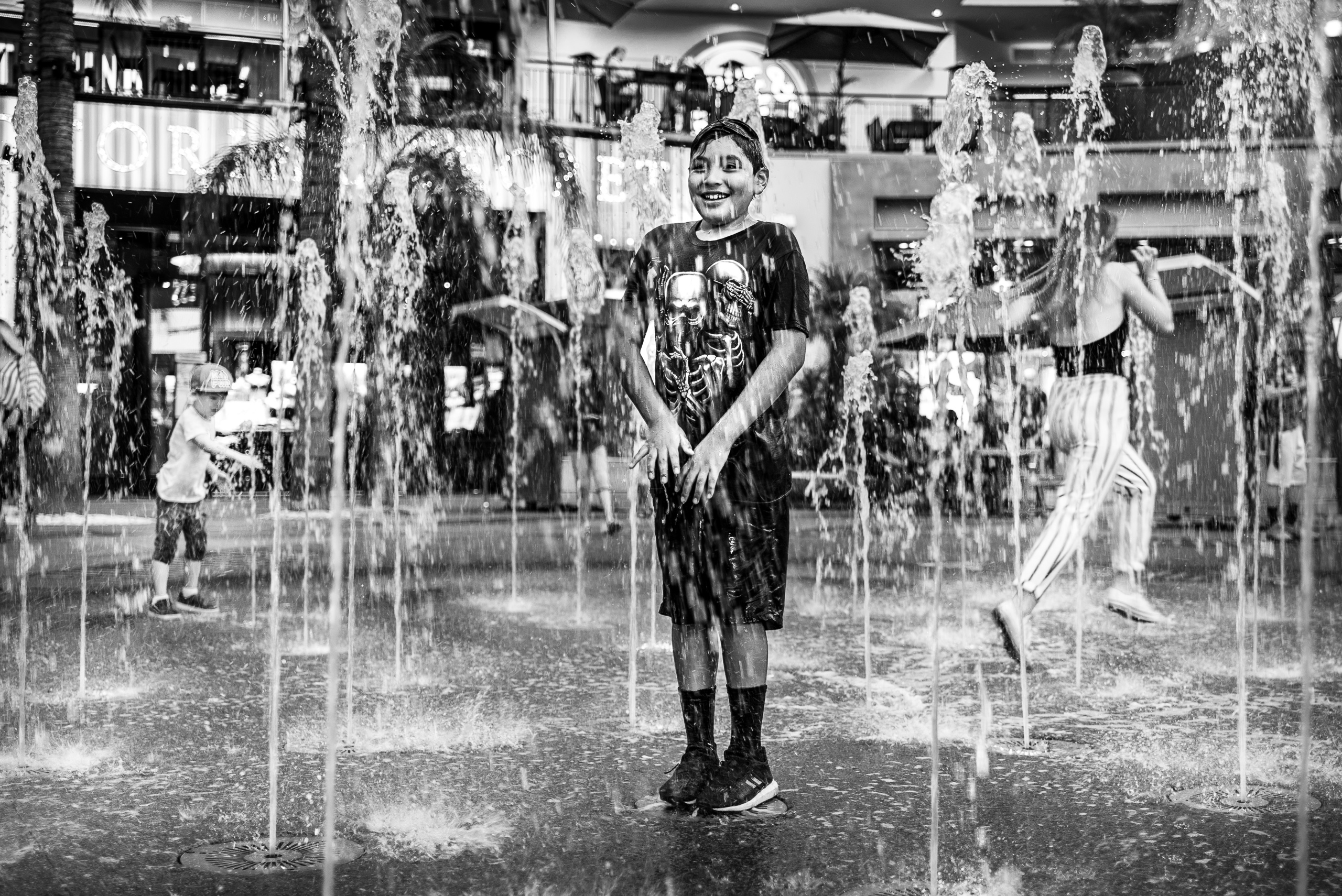 a boy stands in the center of the fountain at Hollywood & Highland and soaks up the cool water on a hot summer night. Meanwhile, behind him, a woman in striped pants makes a fast dash through the fountain, trying to pass through without getting soaked.