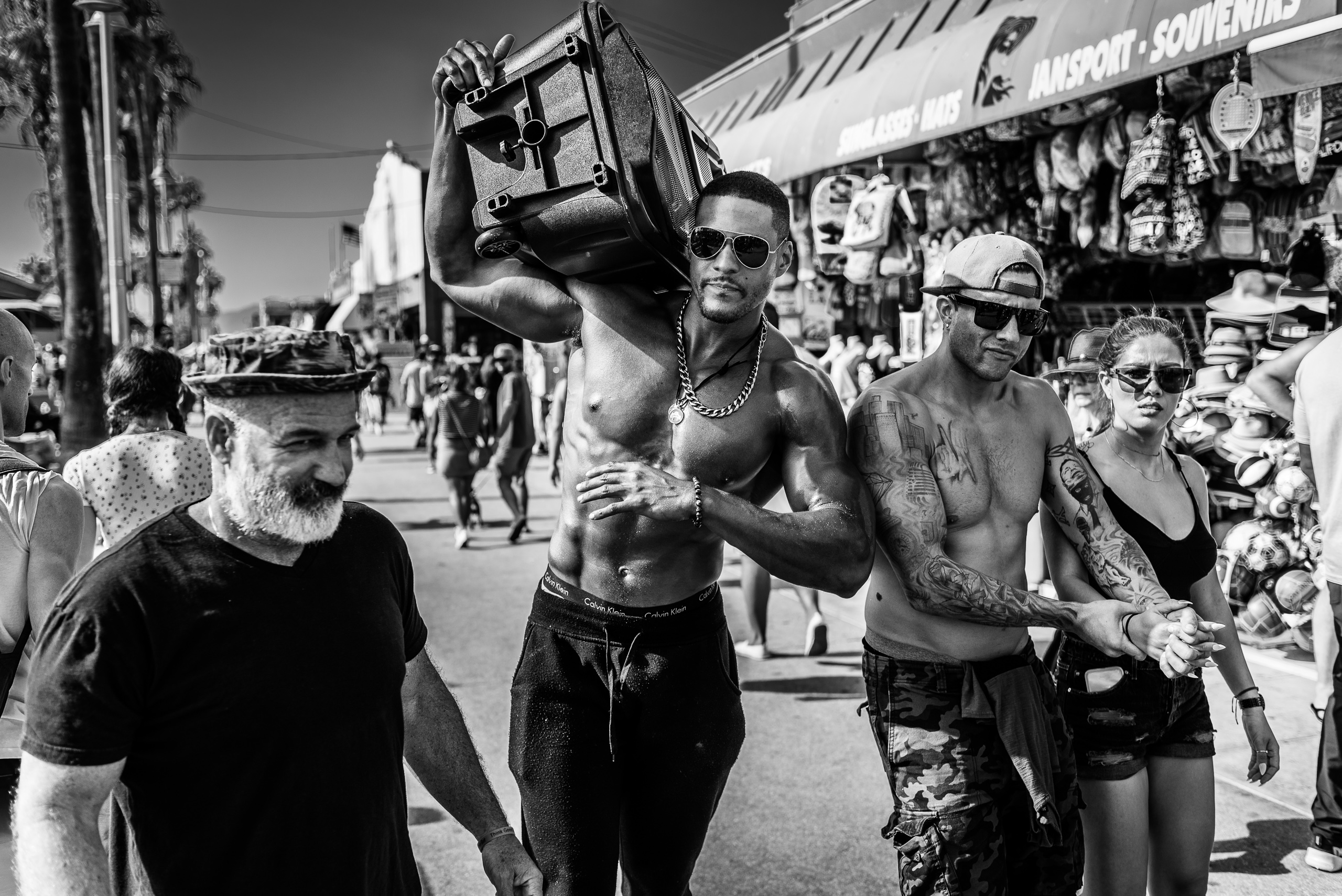 "a man with a really big ""Muscle Beach"" body carries a huge speaker on his shoulder as he walks shirtless down the Venice Beach Boardwalk"