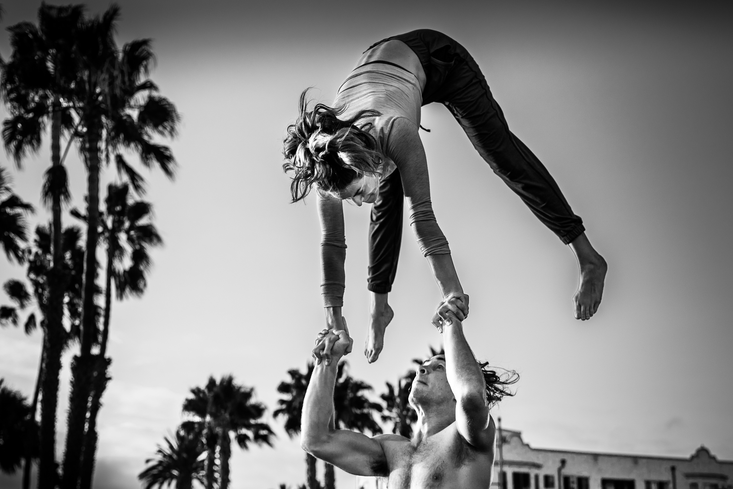 a man holds a woman in the air over his head as she does an inverted acrobatic move